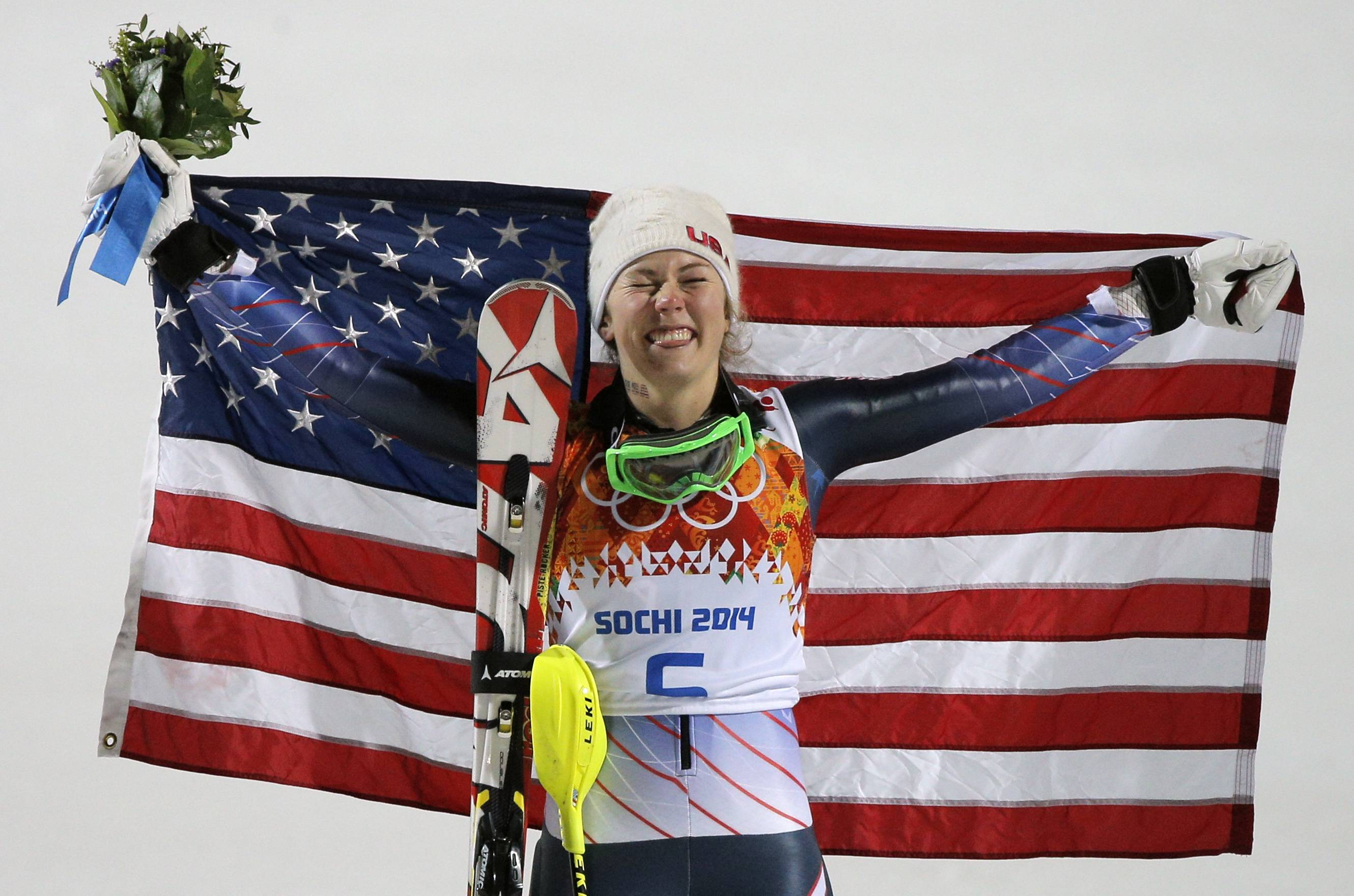 Women's slalom gold medal winner Mikaela Shiffrin of the United States poses for photographers with the American flag.