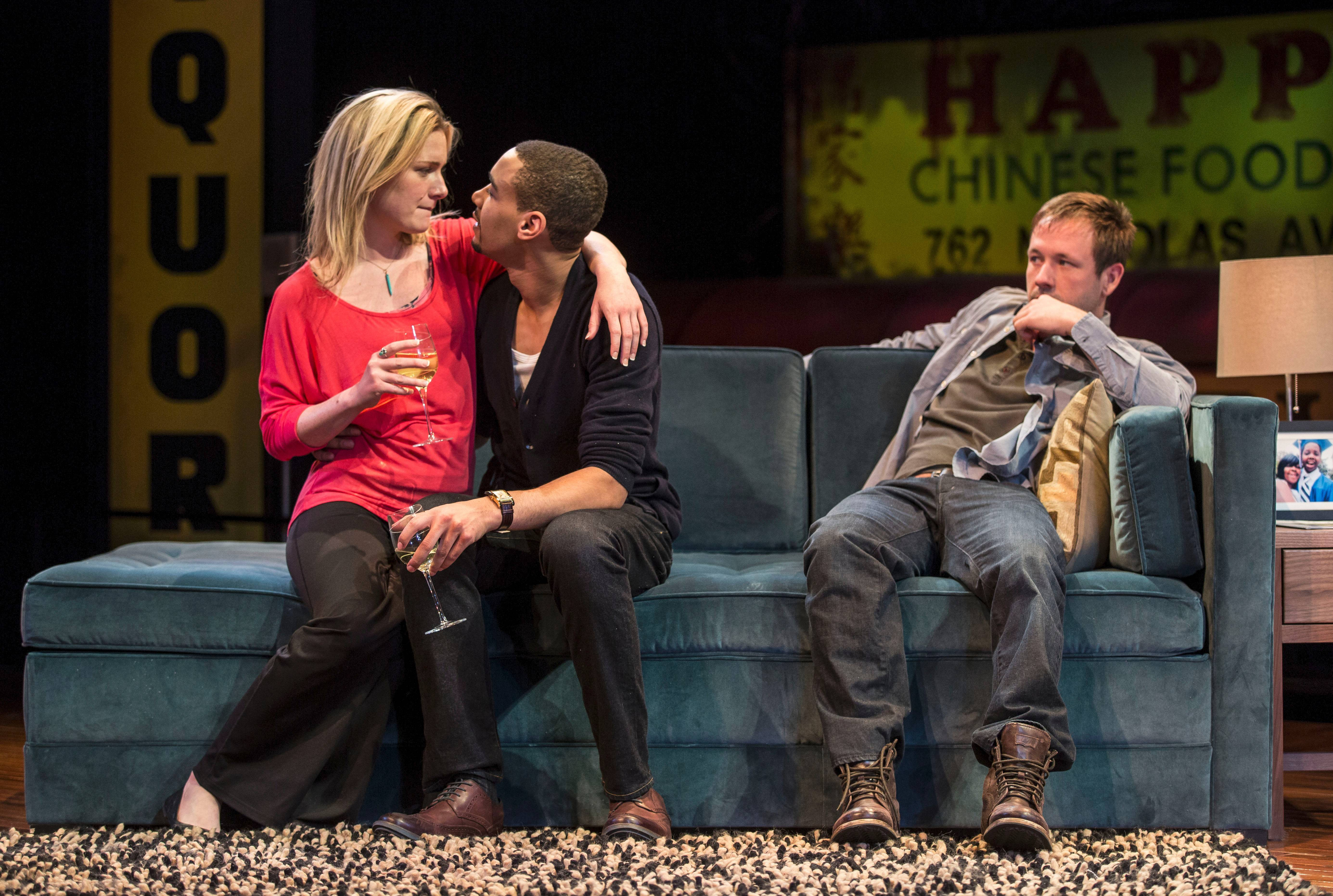 "Suzy (Lee Stark) and Jackson (Eric Lynch) celebrate in their new home while their live-in recovering addict friend, Don (Shane Kenyon), looks on in the Chicago premiere of Tracey Scott Wilson's ""Buzzer"" at the Goodman Theatre."