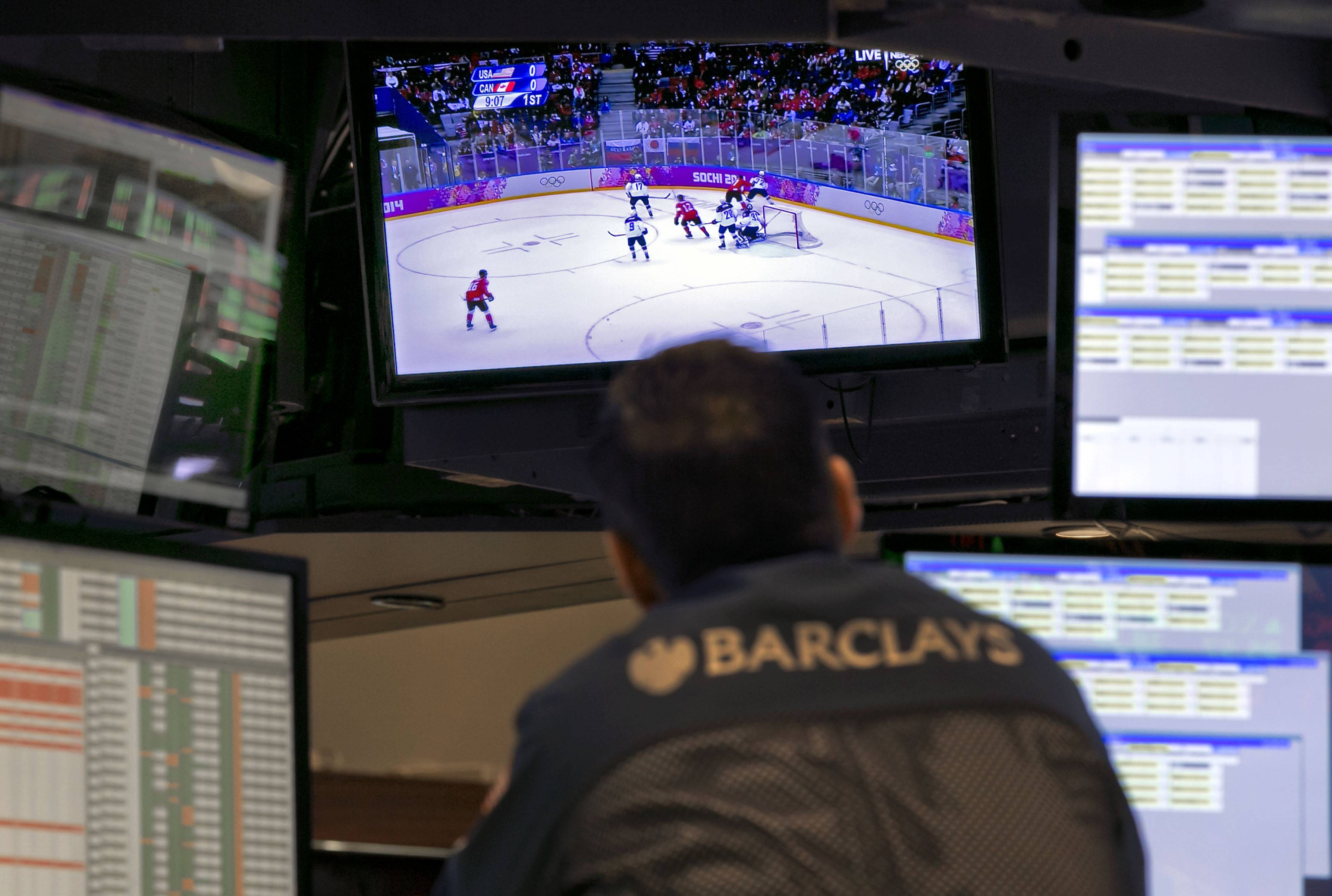 A specialist on the floor of the New York Stock Exchange watches the first period of the Winter Olympics ice hockey game Friday between USA and Canada.