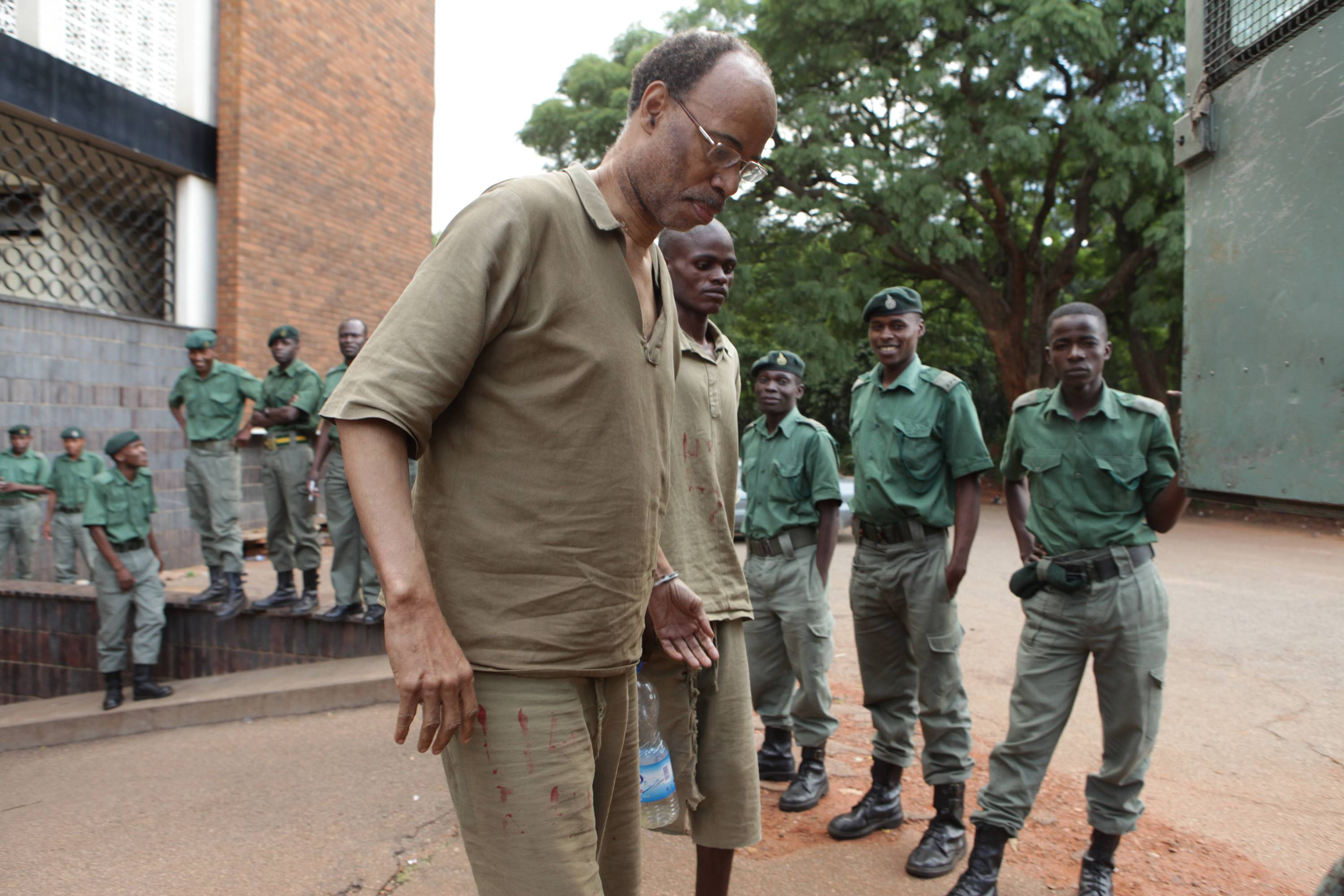 Former U.S. congressman Mel Reynolds, center left, prepares to enter a prison truck Thursday following his court appearance at the magistrates courts in Harare, Zimbabwe. Reynolds was arrested on charges he possessed pornographic material and violating immigration laws.
