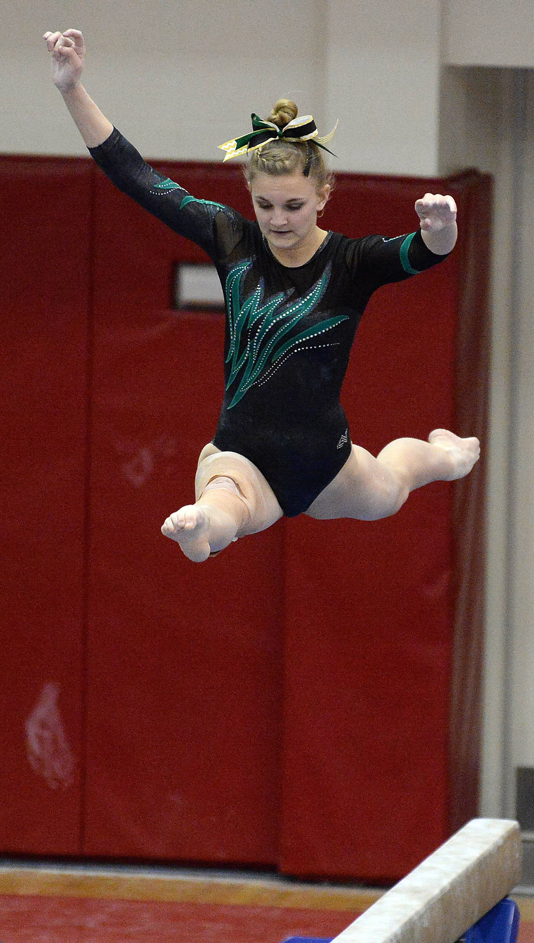 Sydney Plichta of Fremd competes on balance beam in the girls gymnastics state meet in Palatine on Friday.