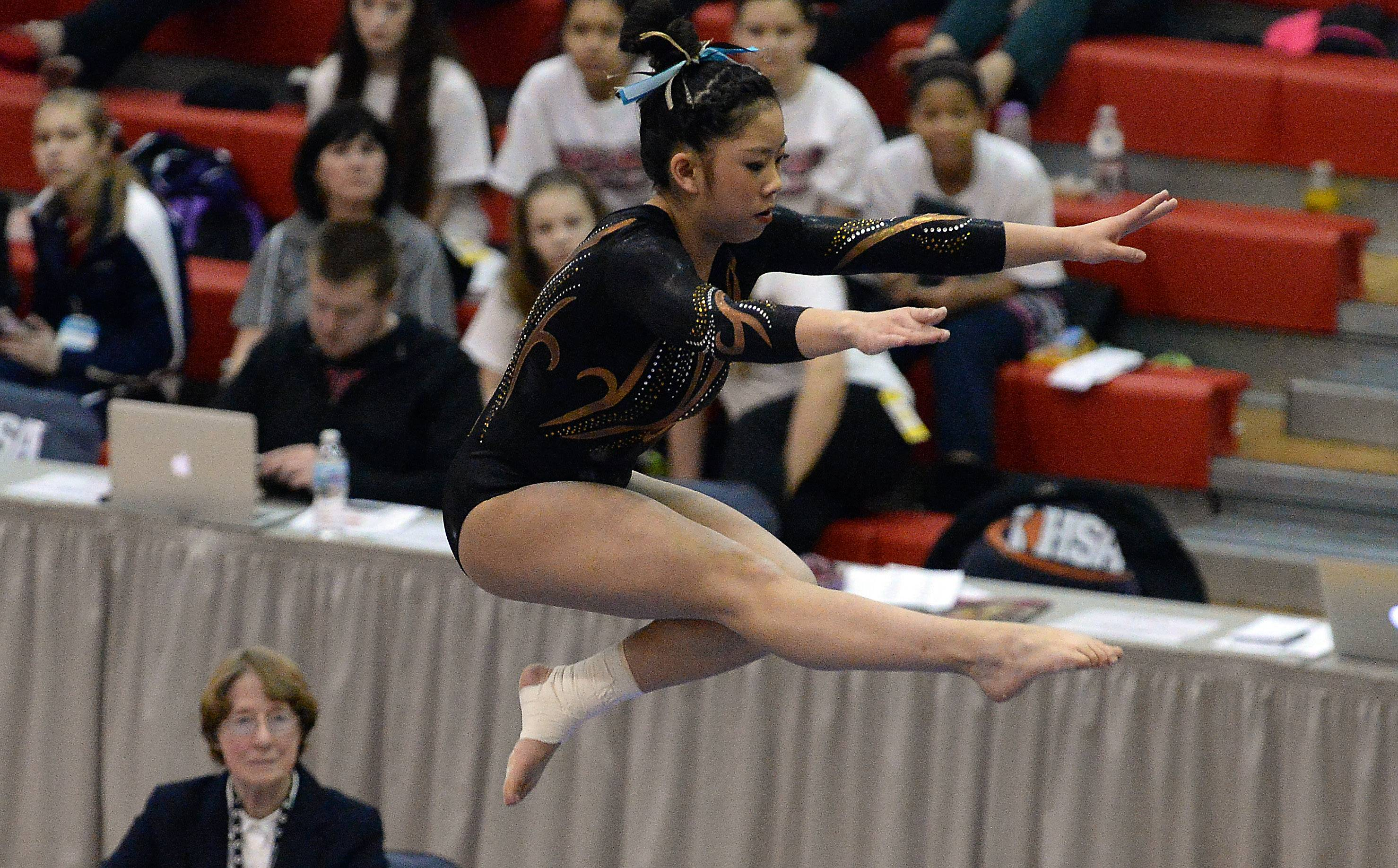 Anna Osowski of Carmel works the balance beam in the girls gymnastics state finals in Palatine on Friday.