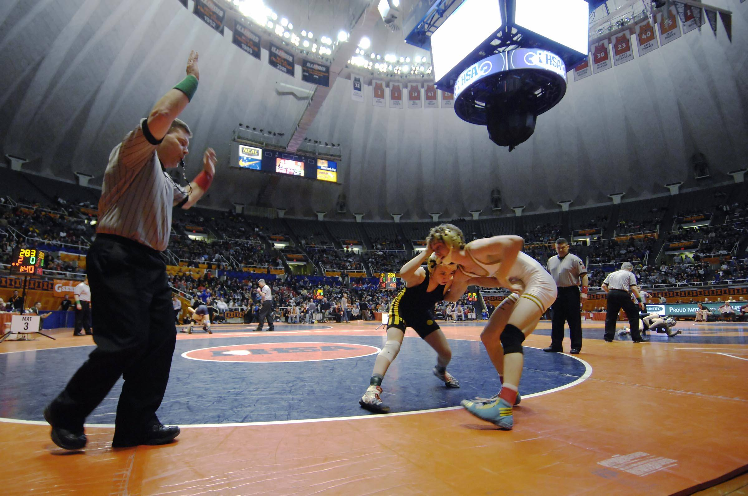 Austin Gomez of Glenbard North High School and Brian Rossi, right,  of Lockport High School compete Friday in the 113-pound weight class semifinals of the wrestling IHSA Class 3A state tournament at State Farm Center in Champaign.