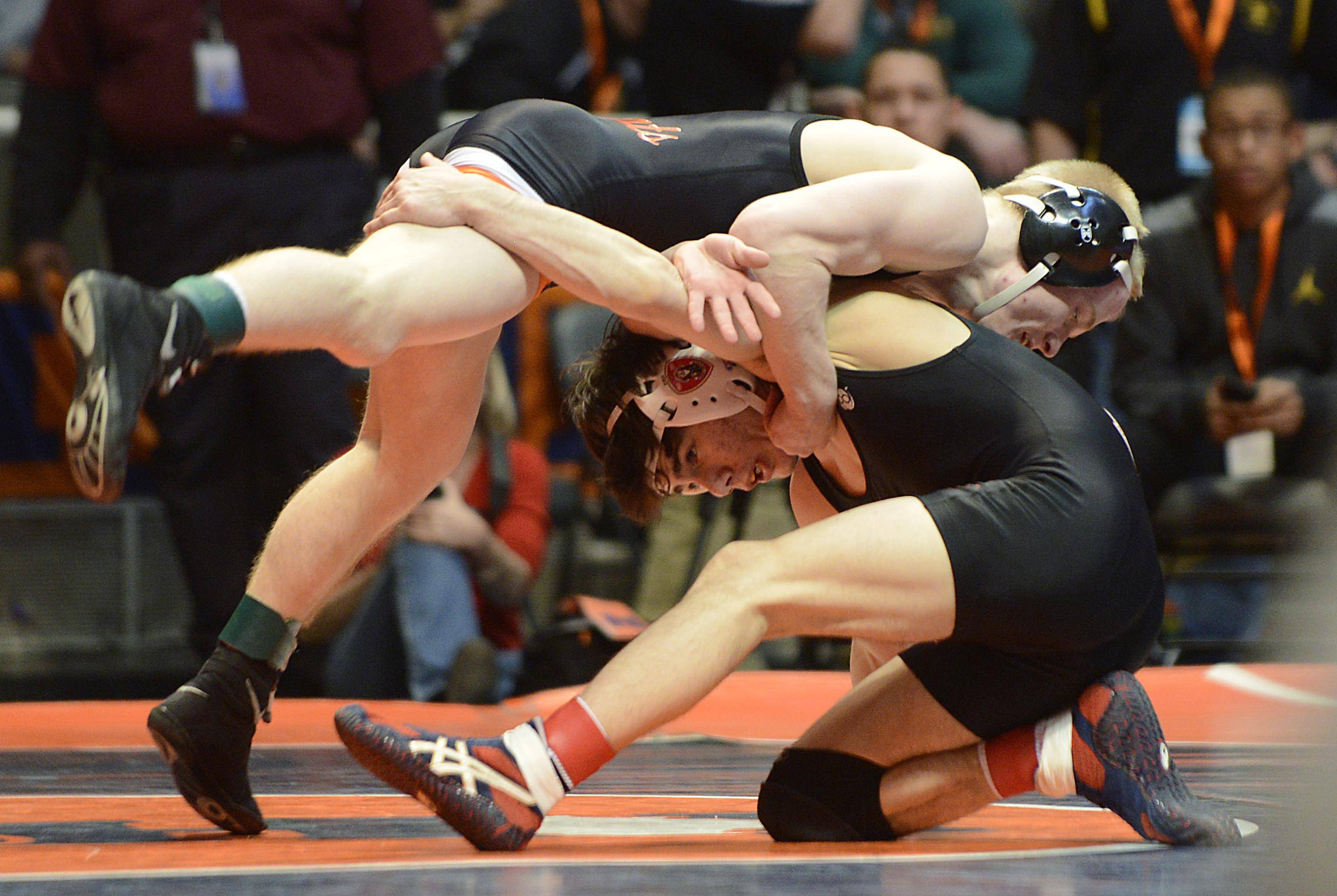 Steve Polakowski of Libertyville High School, top, competes against Mark Duda of Marist High School Friday in the 120-pound weight class semifinals of the wrestling IHSA Class 3A state tournament at State Farm Center in Champaign.