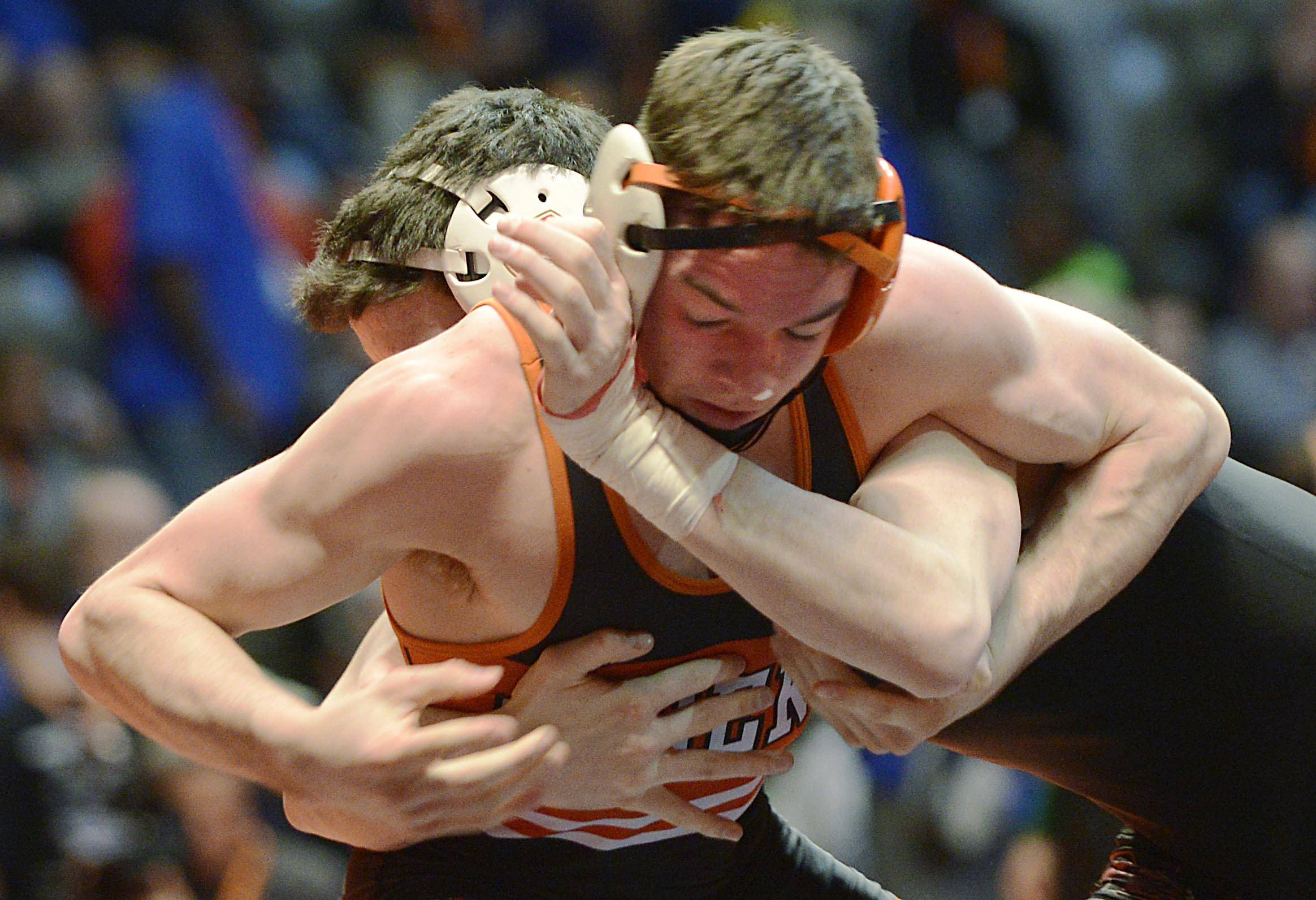 Qarin Johnnic of Wheaton Warrenville South High School competes against Mario Leveille of Marist High School Friday in the 138-pound weight class semifinals of the wrestling IHSA Class 3A state tournament at State Farm Center in Champaign.