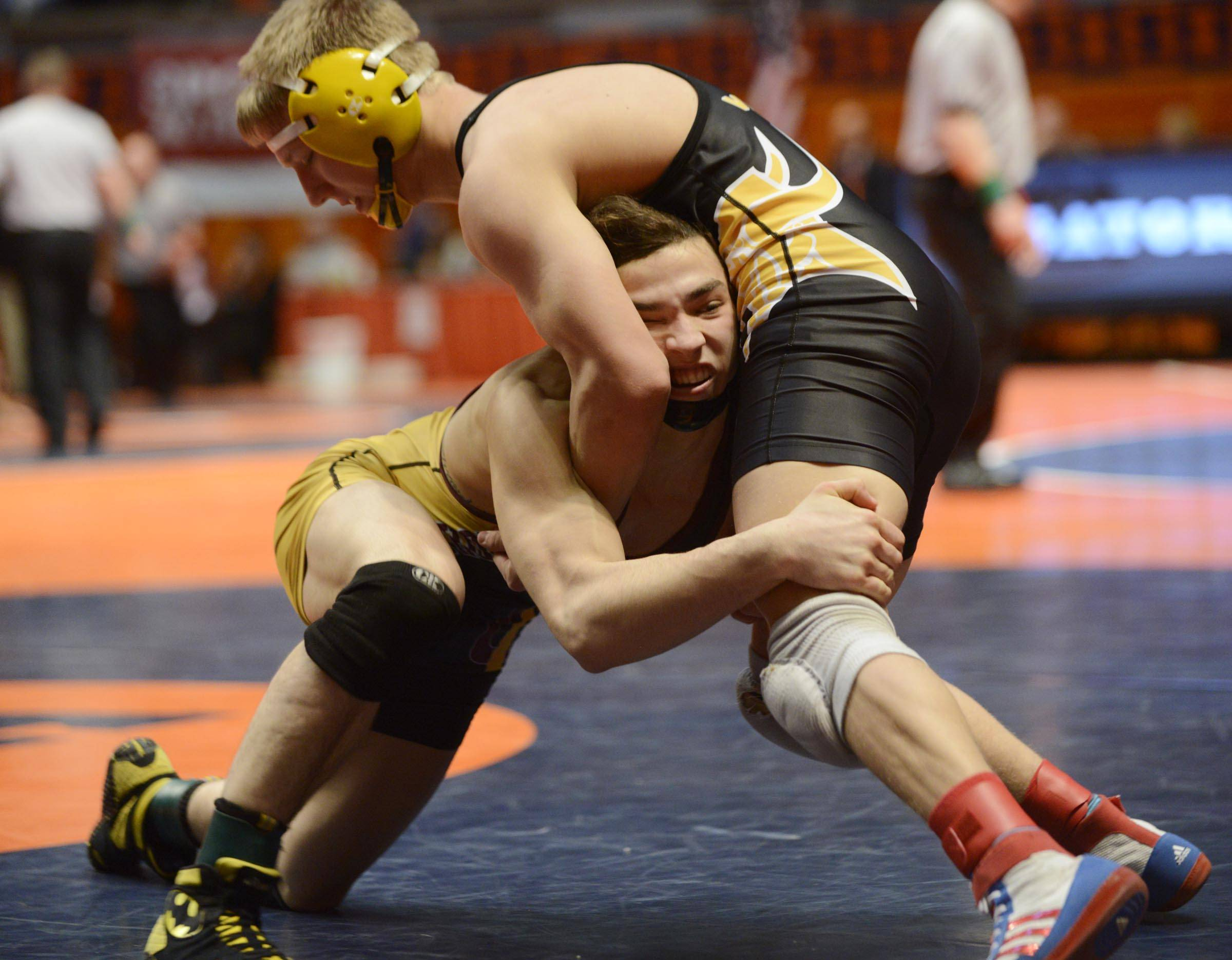 Vincent Turk of Montini High School charges into Johnathan Gahagan of St. Laurence High School Friday in the 138-pound weight class semifinals of the wrestling IHSA Class 2A state tournament at State Farm Center in Champaign.