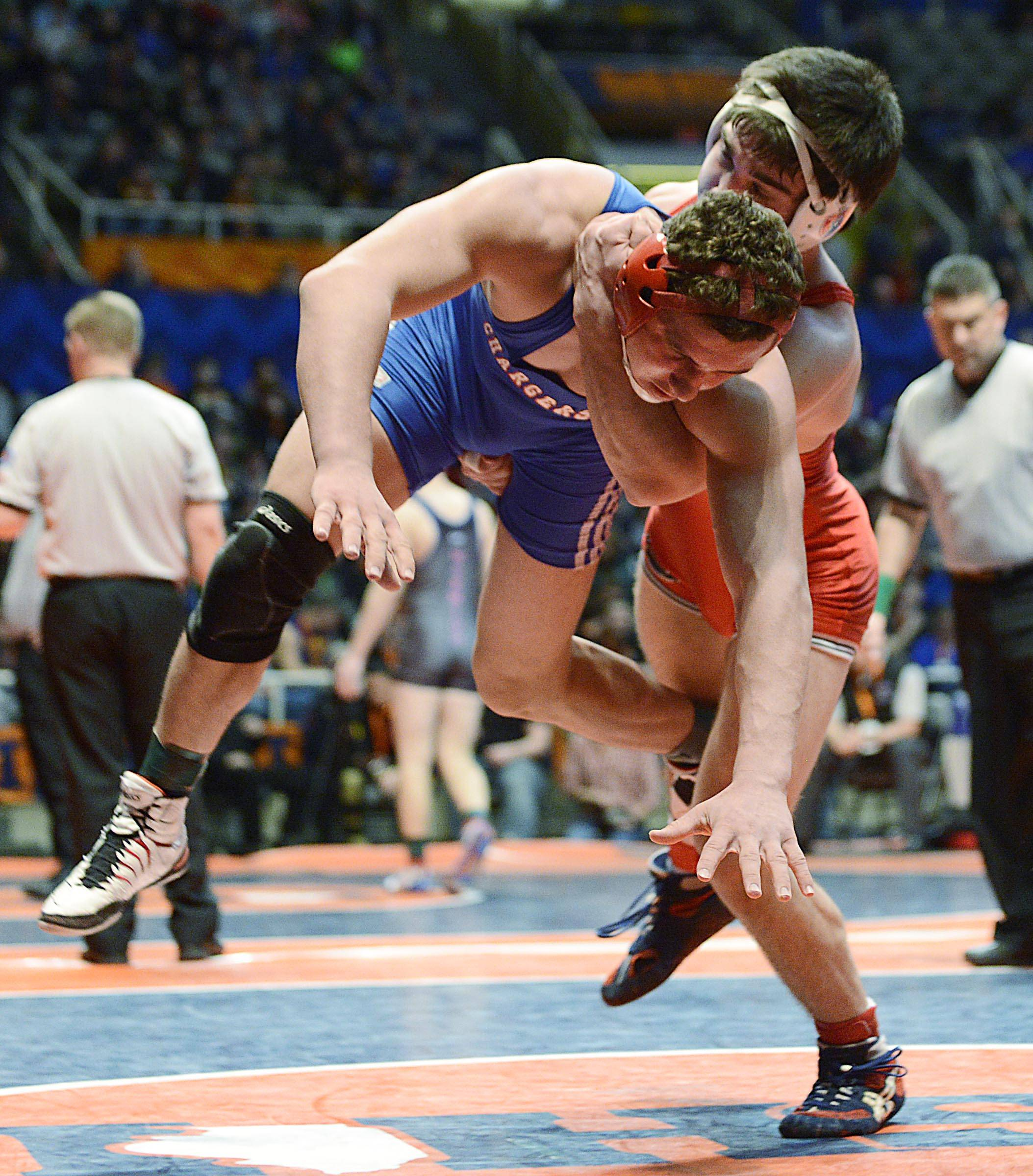 Christian Brunner of  Dundee-Crown High School is lifted and thrown by Alex Benoit of Marist High School Friday in the 182-pound weight class semifinals of the wrestling IHSA Class 3A state tournament at State Farm Center in Champaign.