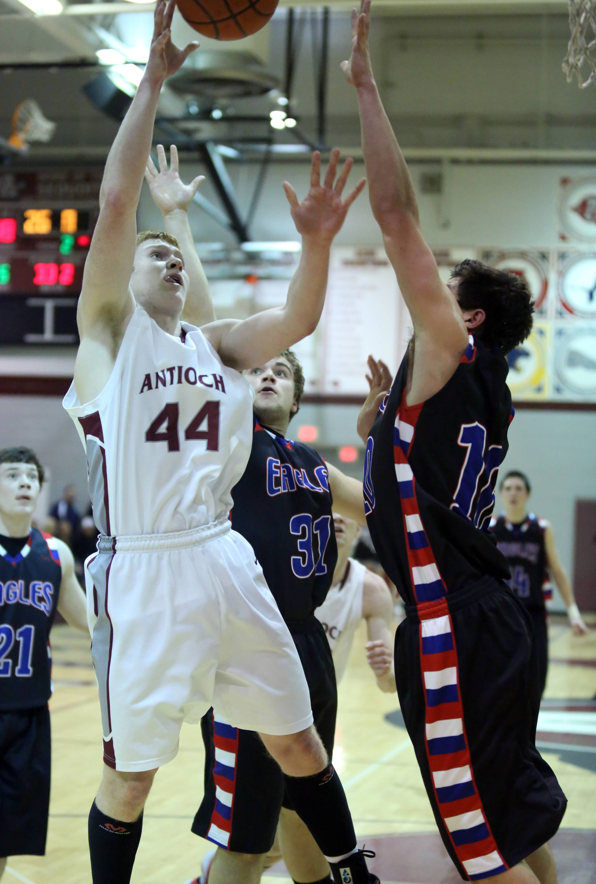 Antioch forward Jack Kovach grabs a rebound against Lakes guard Benett Haviland.