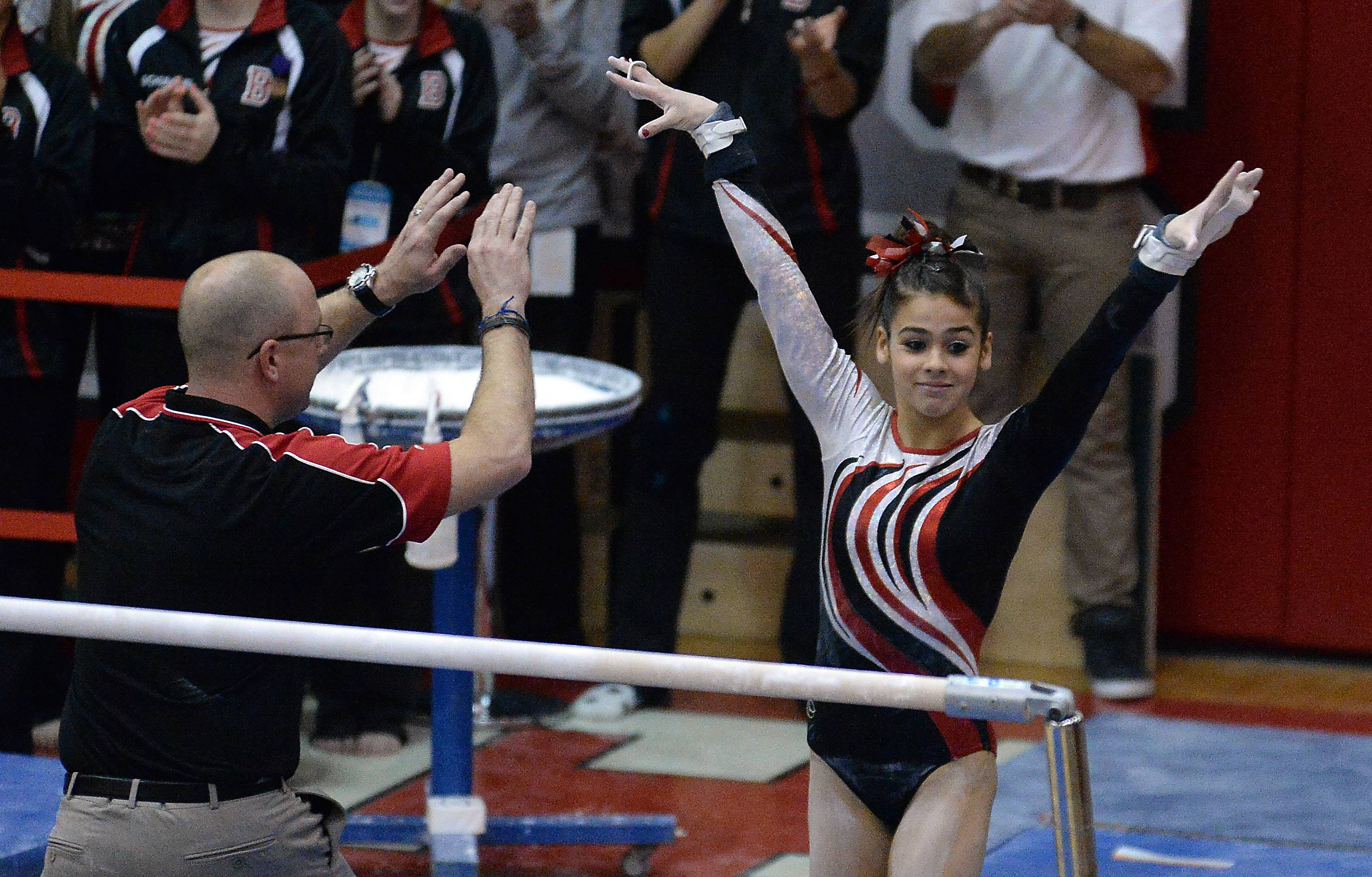 Barrington's Abby Hasanov celebrates her routine with her coach after competing on the uneven parallel bars.