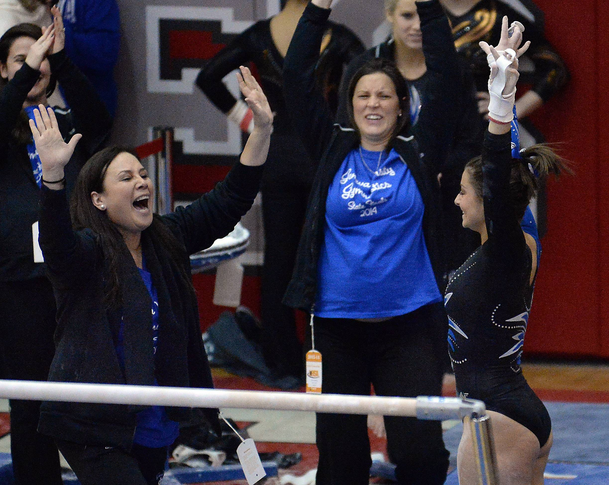 Geneva's Dominique Brognia celebrates her routine with her coach after competing on the uneven parallel bars.