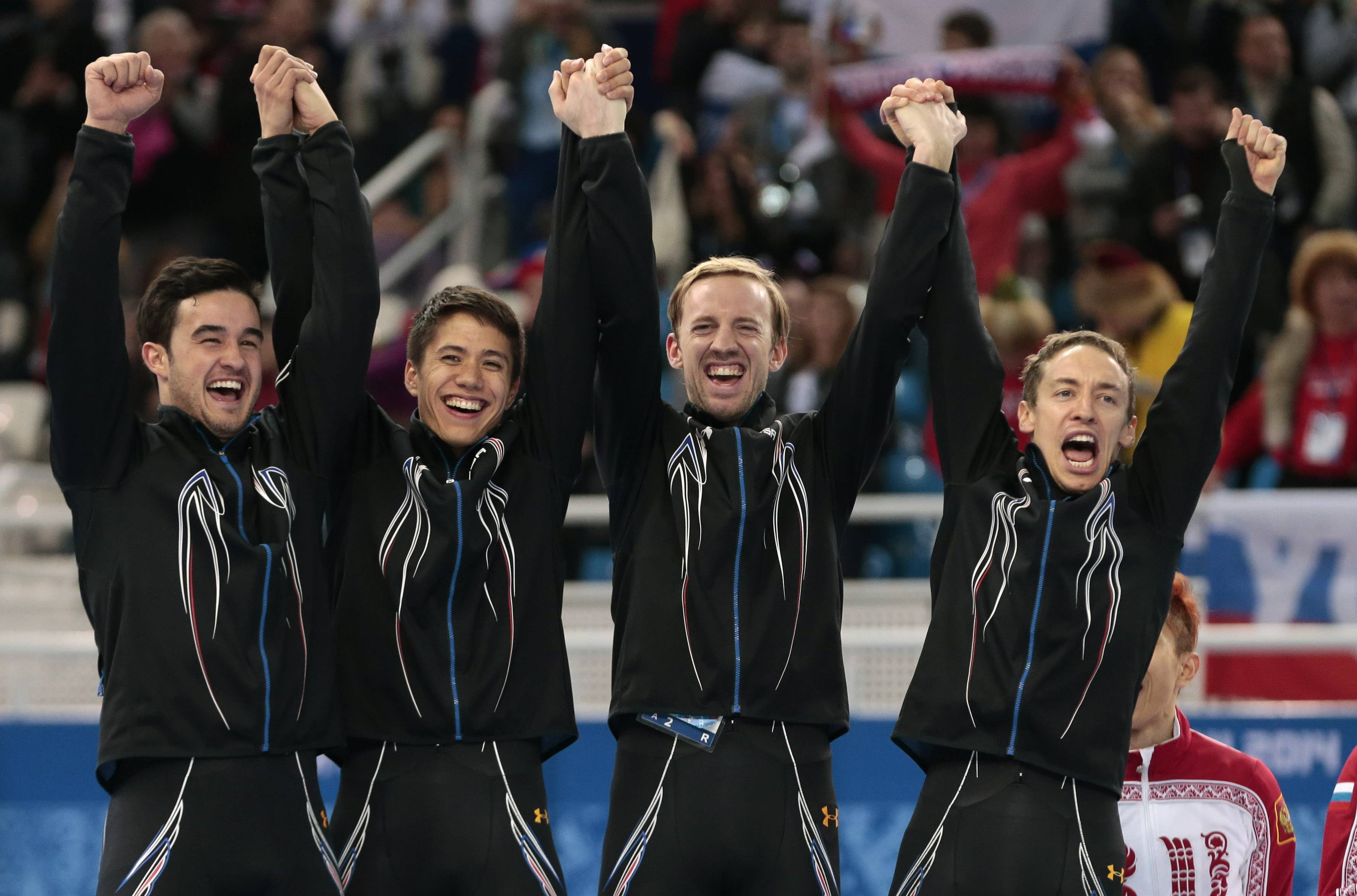 Members of U.S. team celebrate on the podium Friday after receiving their silver medals for the 5000-meter short track speedskating relay in Sochi.