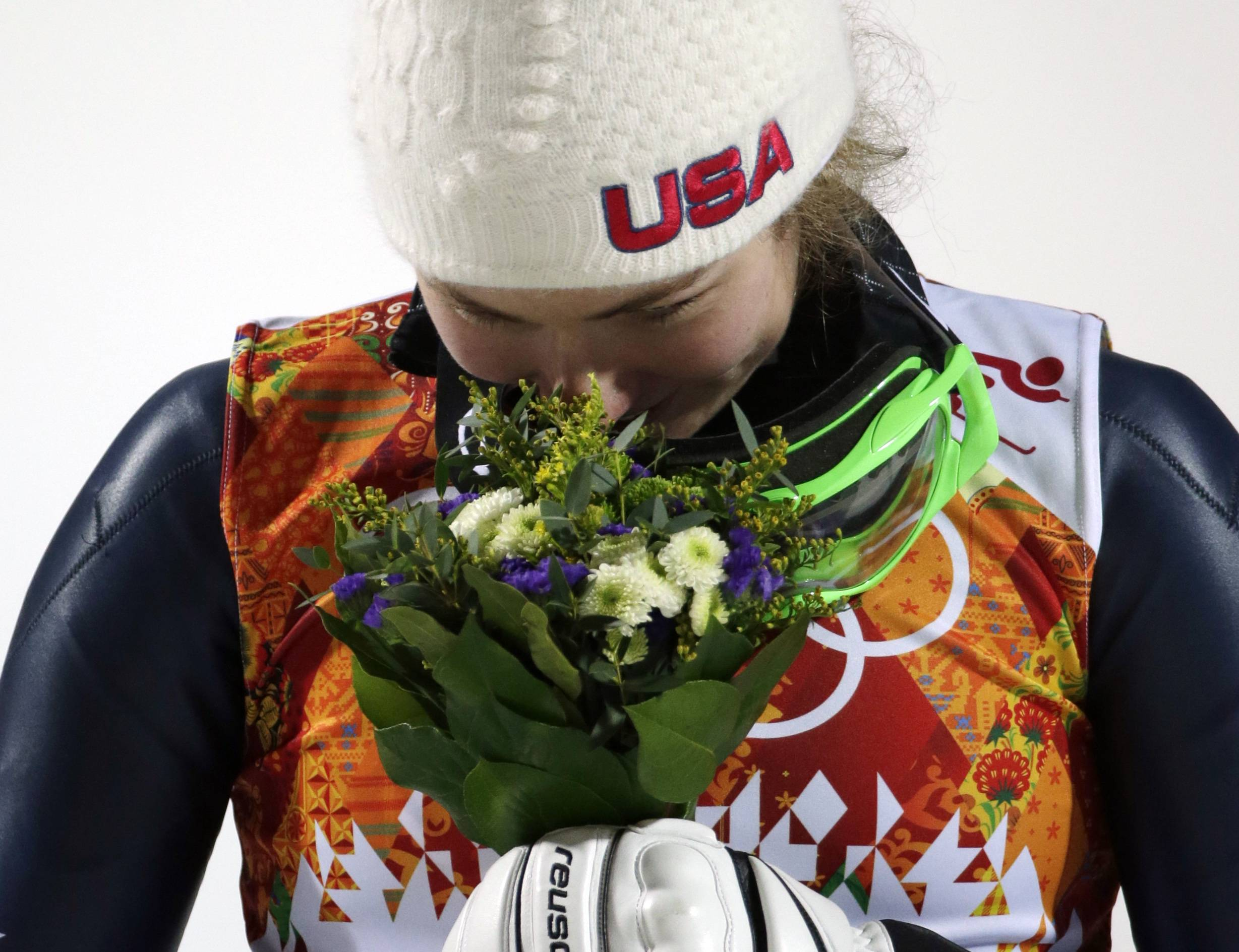 Women's slalom gold medal winner Mikaela Shiffrin of the United States smells her bouquet during a flower ceremony.