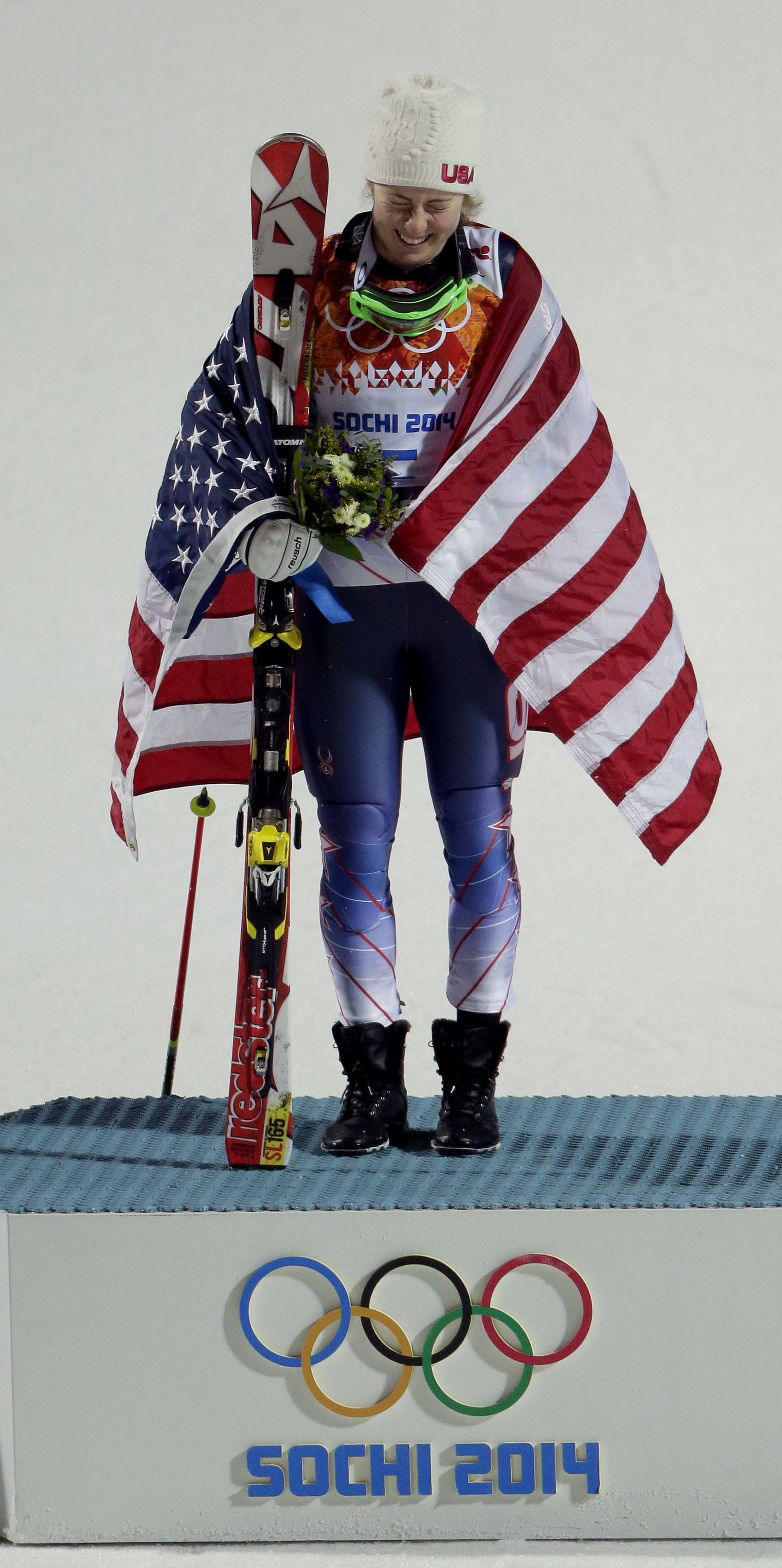 Women's gold medalist, United States' Mikaela Shiffrin, reacts after dropping her ski pole during the flower ceremony for the women's slalom.