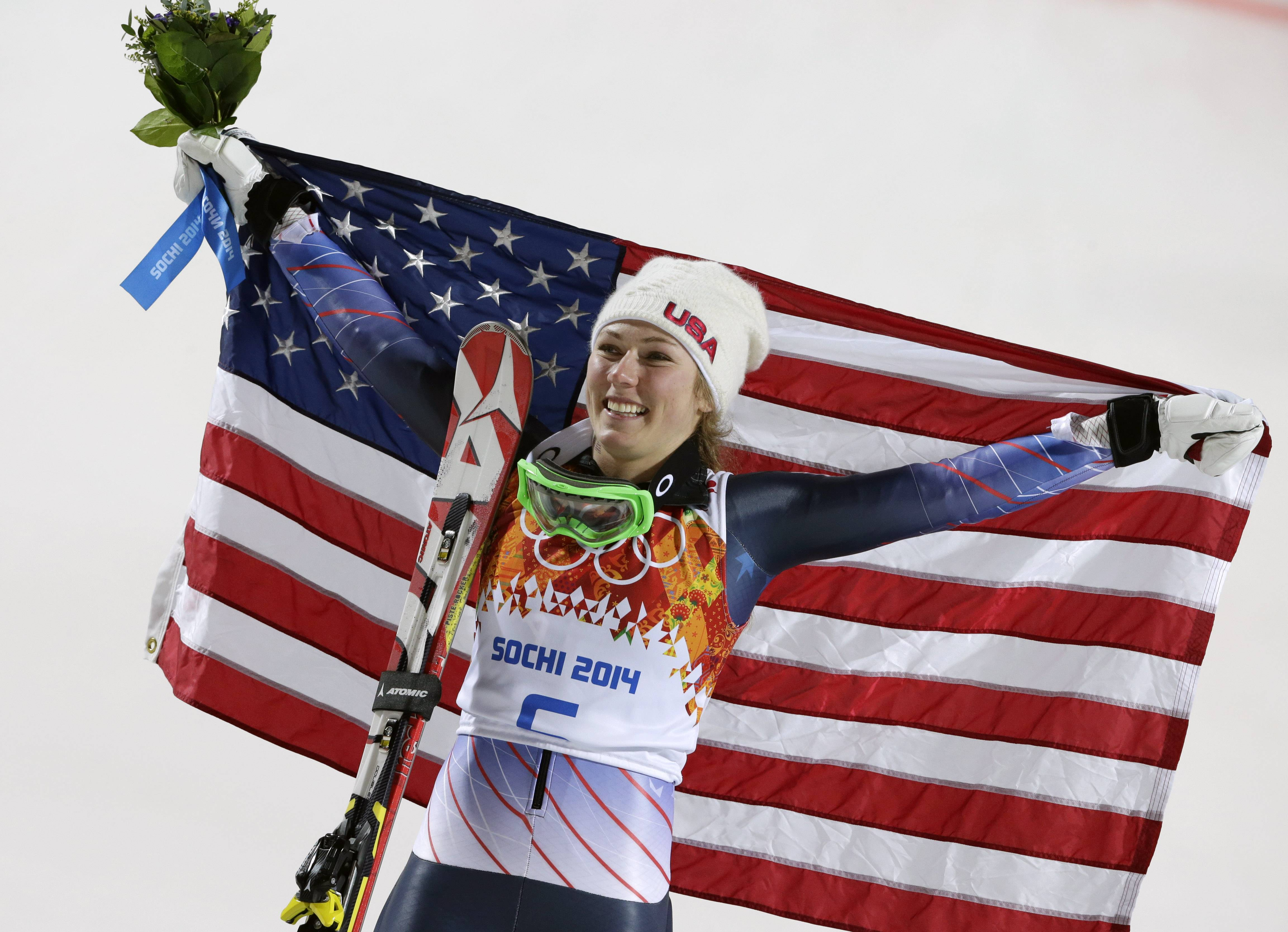 Women's slalom gold medal winner Mikaela Shiffrin of the United States poses for photographers with the U.S. flag.
