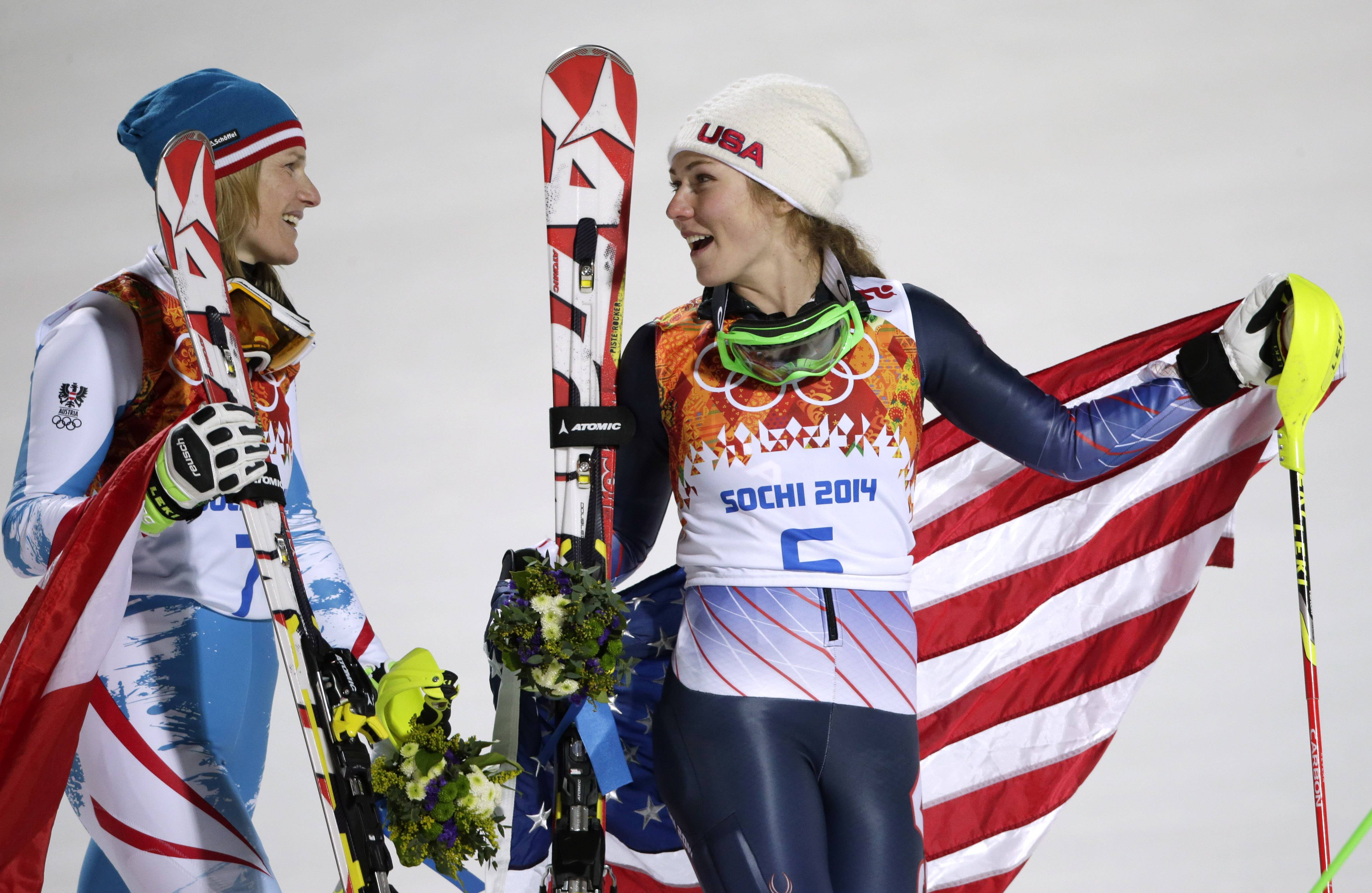 Women's slalom silver medal winner Marlies Schild of Austria, left, and gold medal winner Mikaela Shiffrin of the United States leave the podium after a flower ceremony.
