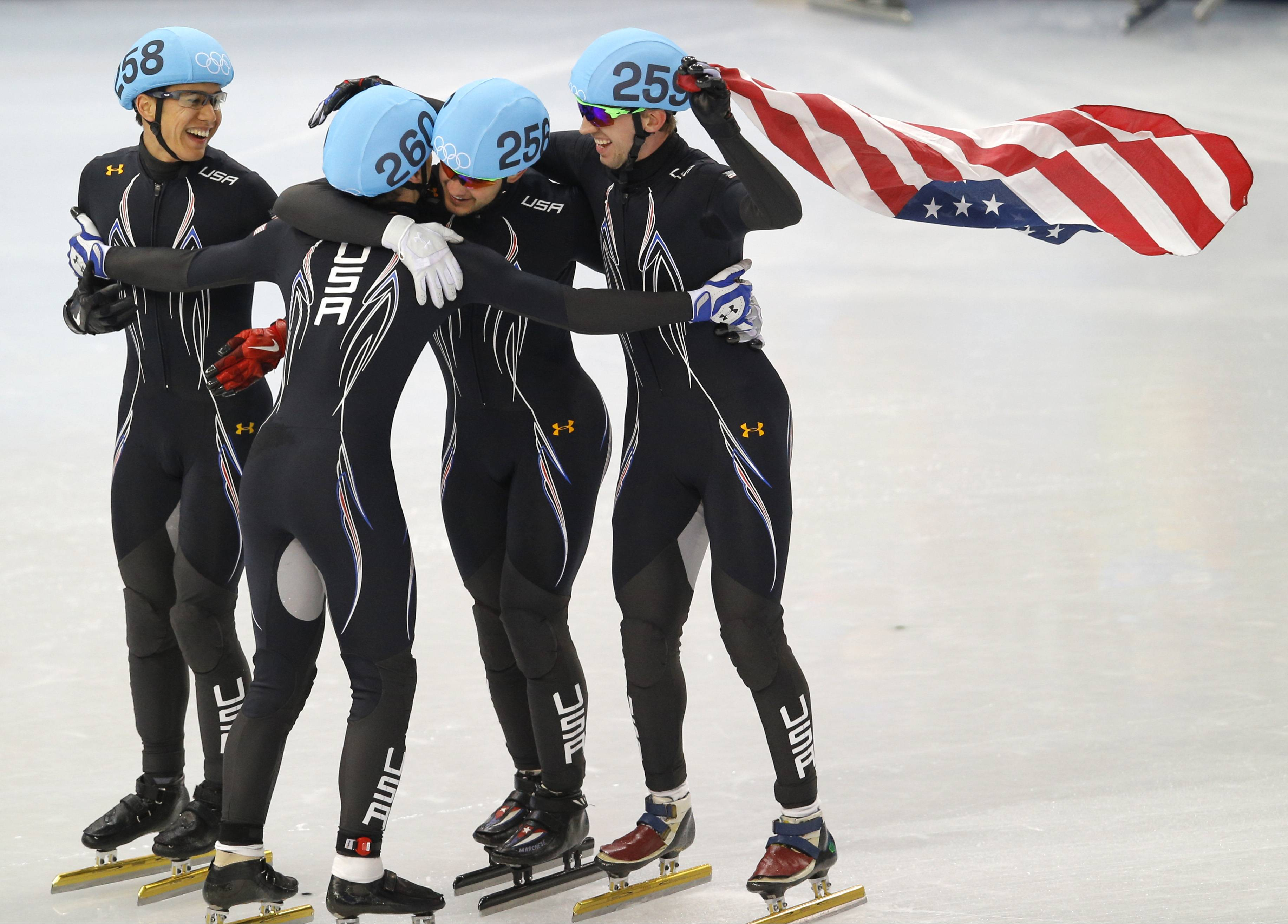 From left, J.R. Celski of the United States, Jordan Malone of the United States, Eduardo Alvarez of the United States and Chris Creveling of the United States celebrate their second place finish in the men's 5000m short track speedskating relay final.
