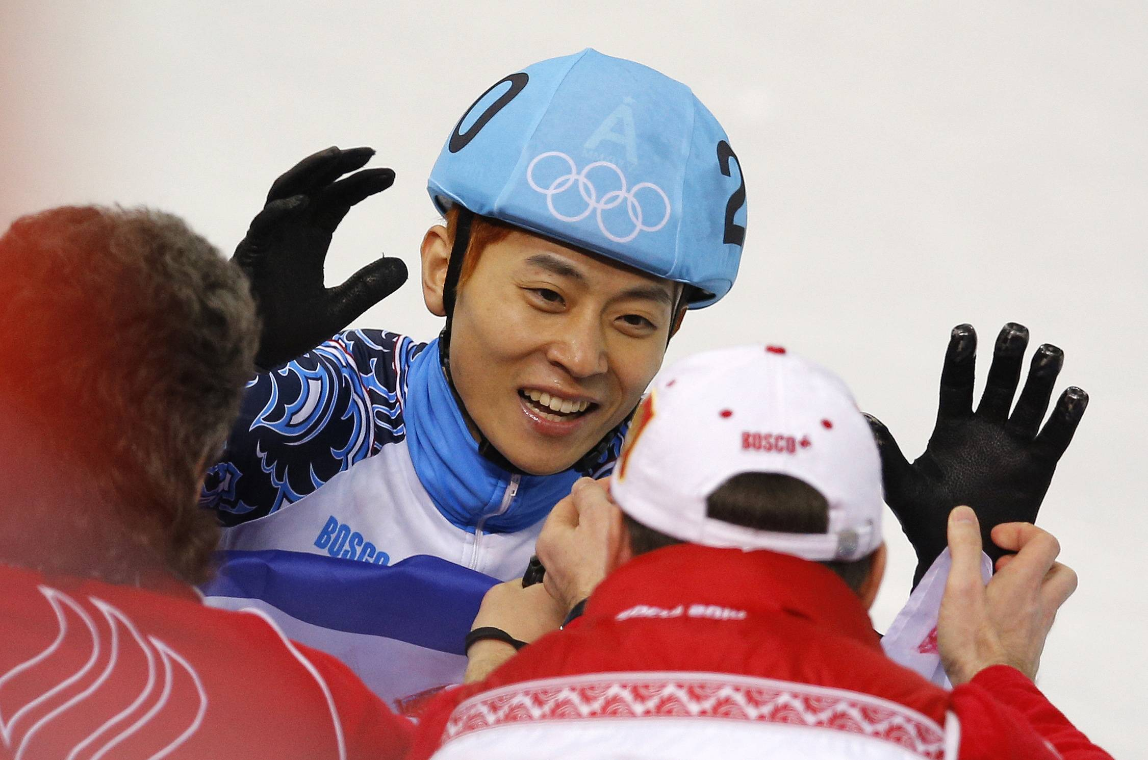 Victor An of Russia, center, celebrates with team members after he finished first in the men's 500m short track speedskating final.