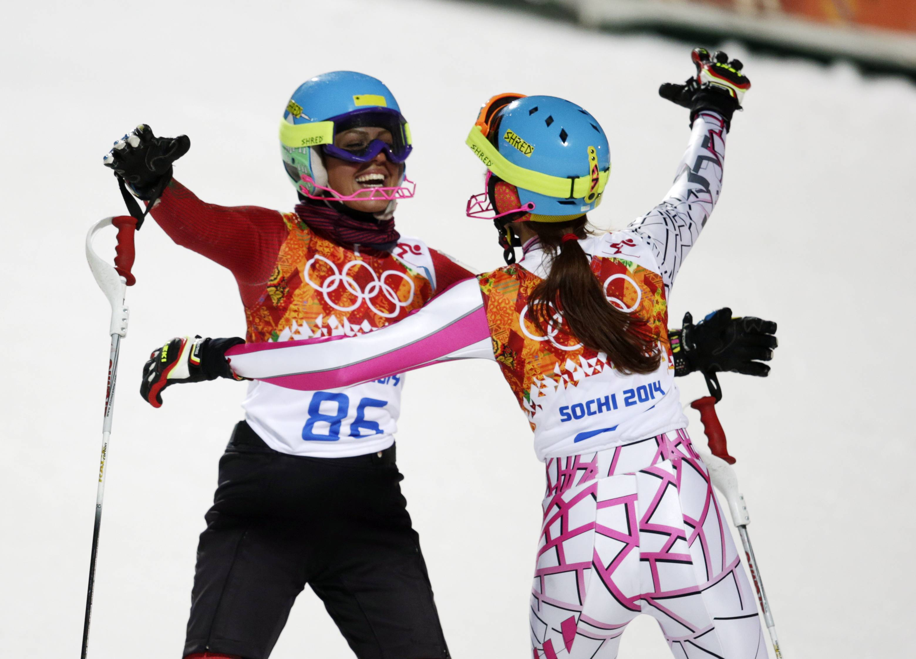 Iran's Forough Abbasi, left, and Lebanon's Jacky Chamoun embrace after finishing the second run of the women's slalom .