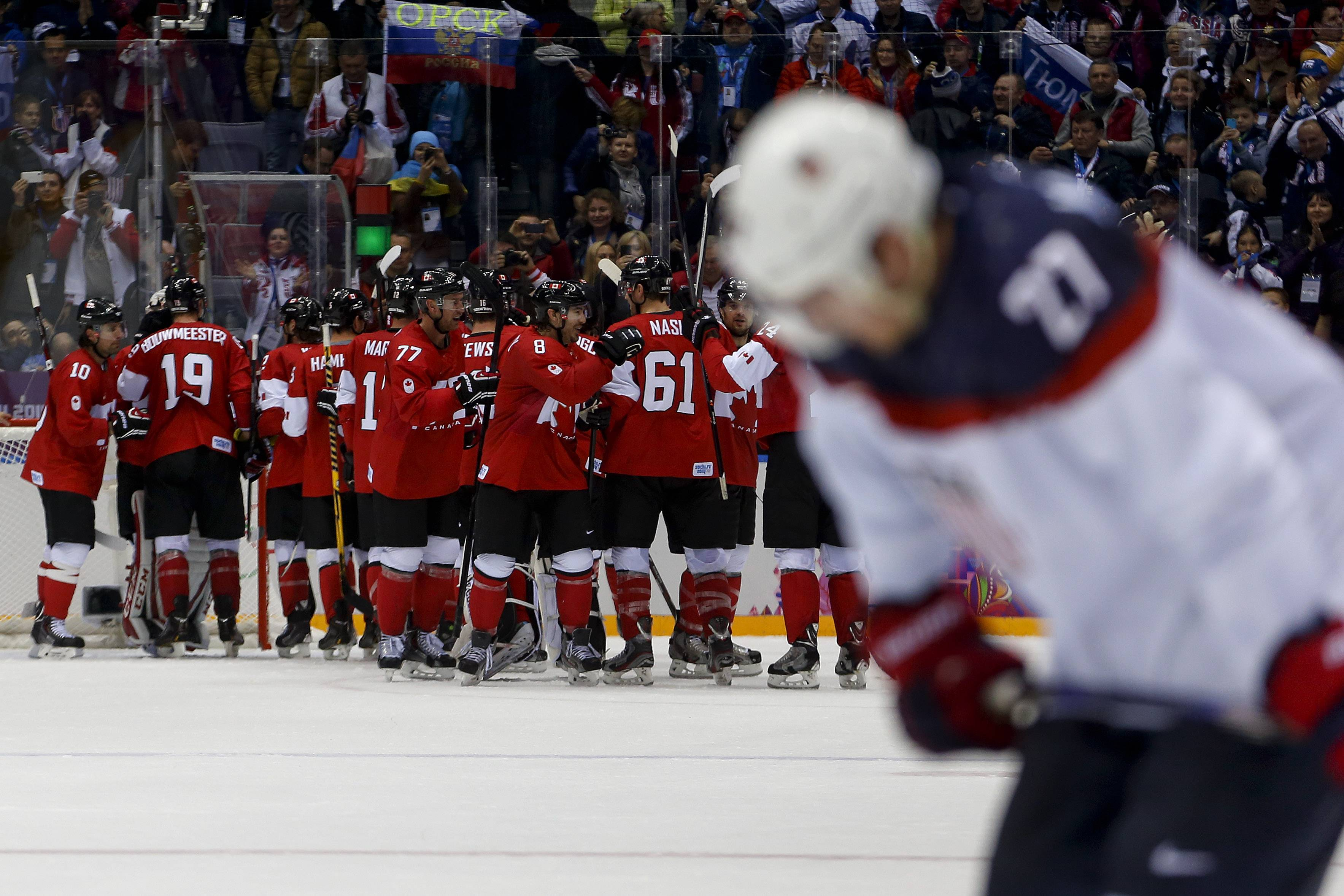 Team Canada celebrates after beating the USA 1-0 in a men's semifinal ice hockey game.