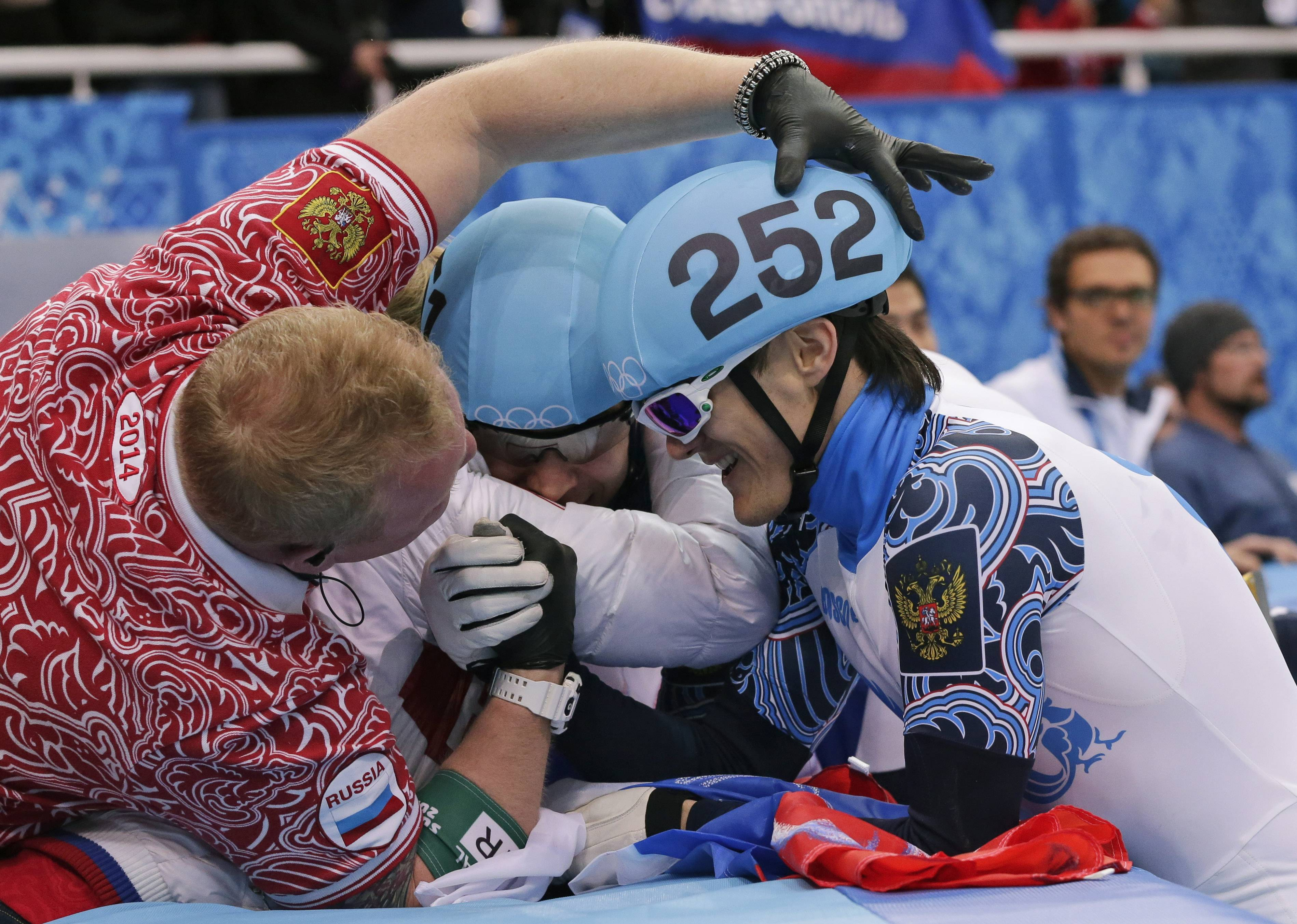 Vladimir Grigorev of Russia, right, celebrates with teammates after the won the men's 5000m short track speedskating relay final.