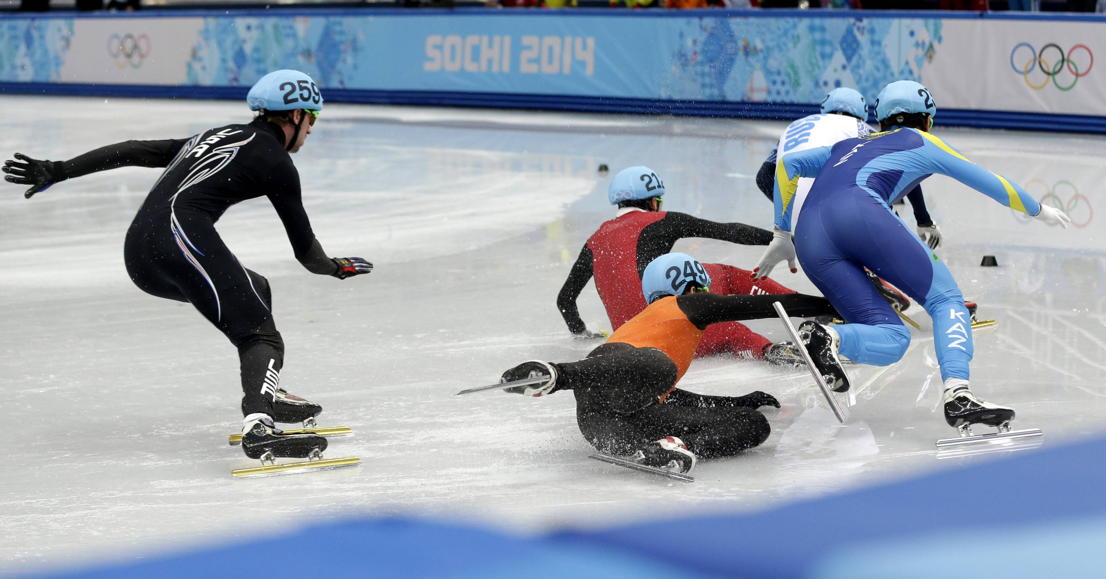 Freek van der Wart of the Netherlands, center foreground, and Wu Dajing of China, center back, crash out in the men's 5000m short track speedskating relay final.
