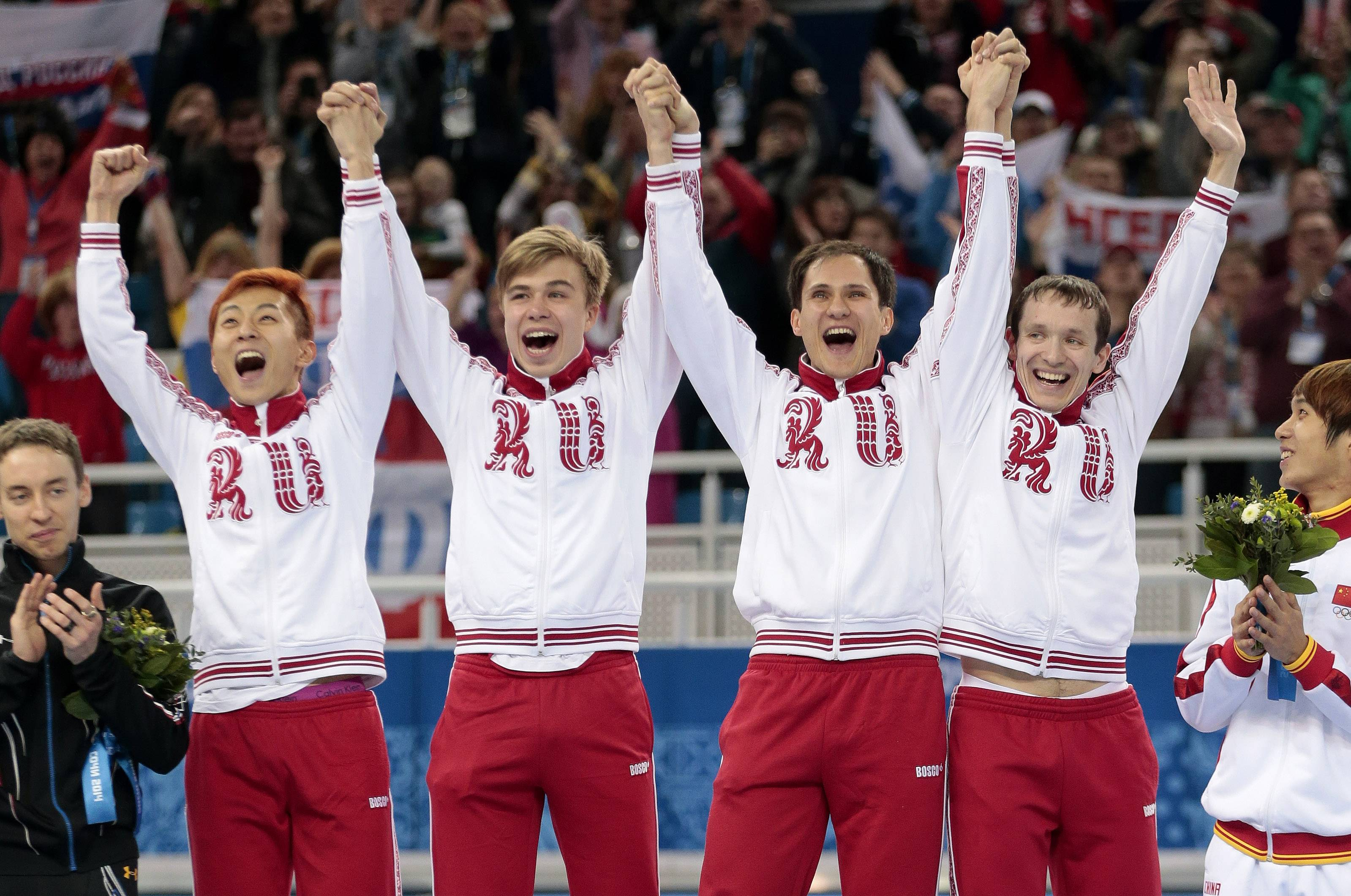 The Russian team celebrates on the podium after they placed first for the men's 5000m short track speedskating relay final.