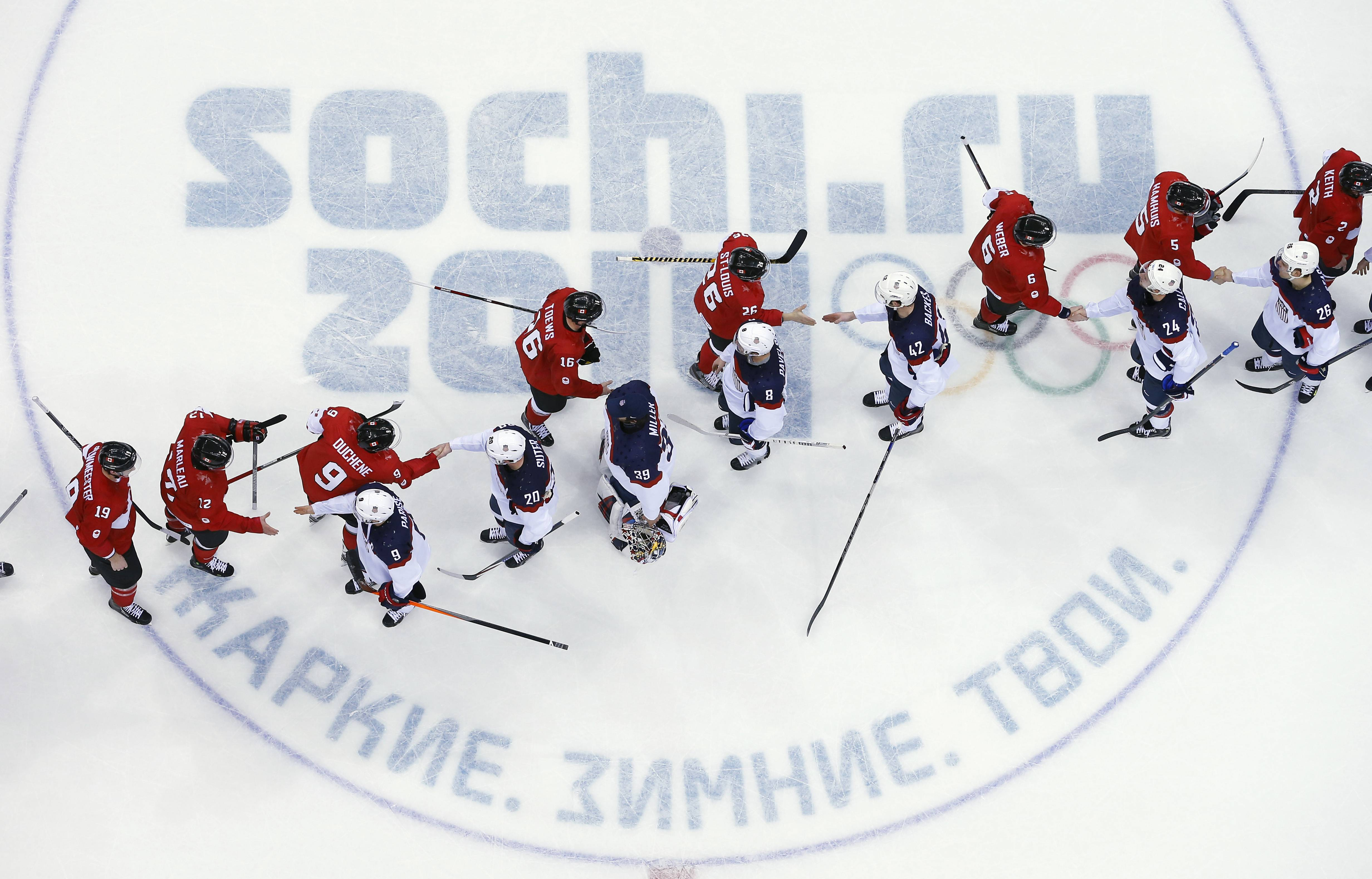USA and Canada players shake hands after a men's semifinal ice hockey game.