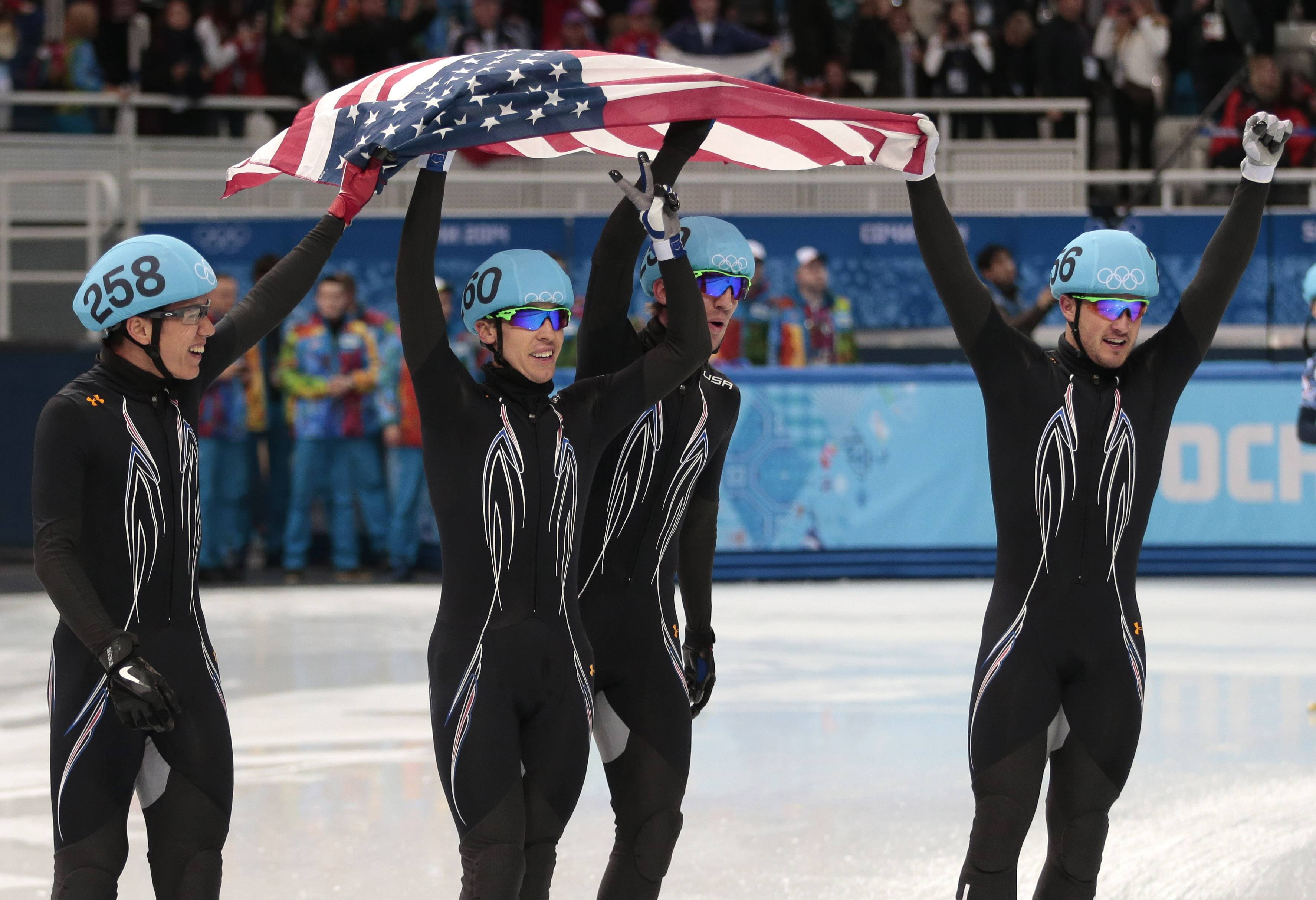 From left, J.R. Celski of the United States, Jordan Malone of the United States, Chris Creveling of the United States and Eduardo Alvarez of the United States celebrate their second place in the men's 5000m short track speedskating relay final.