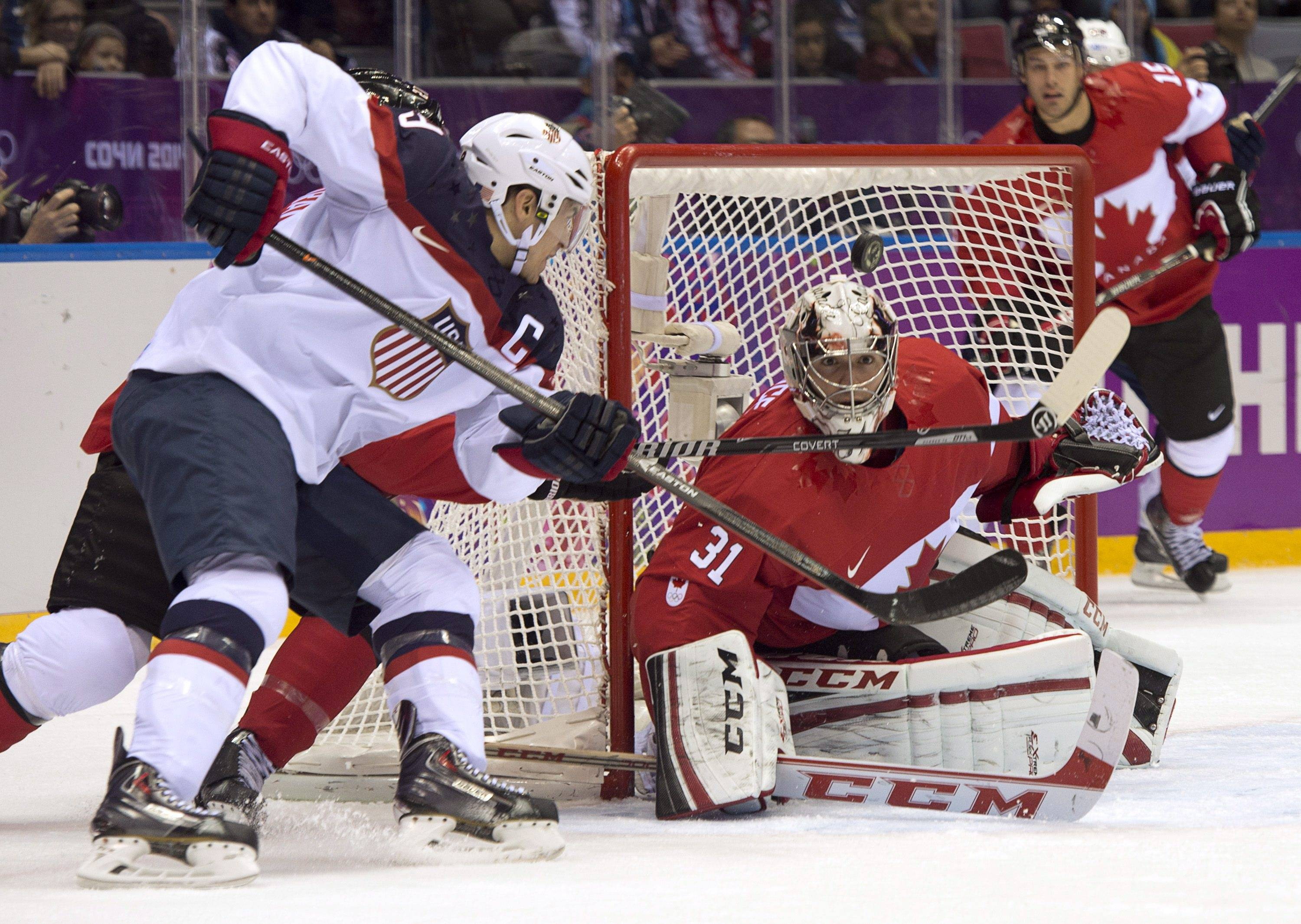 Goalie Carey Price of Canada keeps his eye on the puck as Zach Parise of the United States shoots.