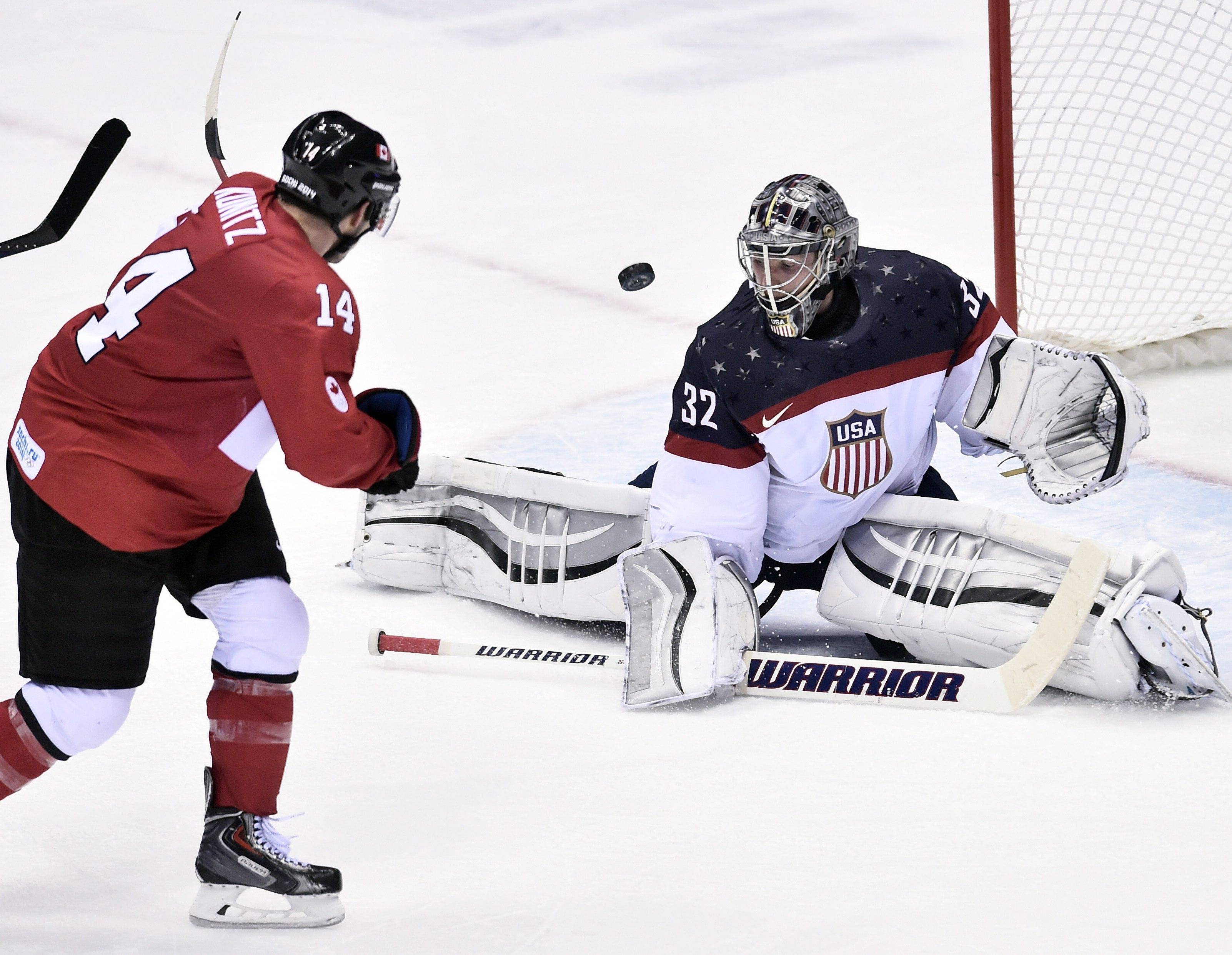 A Canadian shot is stopped by United States' goaltender Jonathan Quick of the United States.