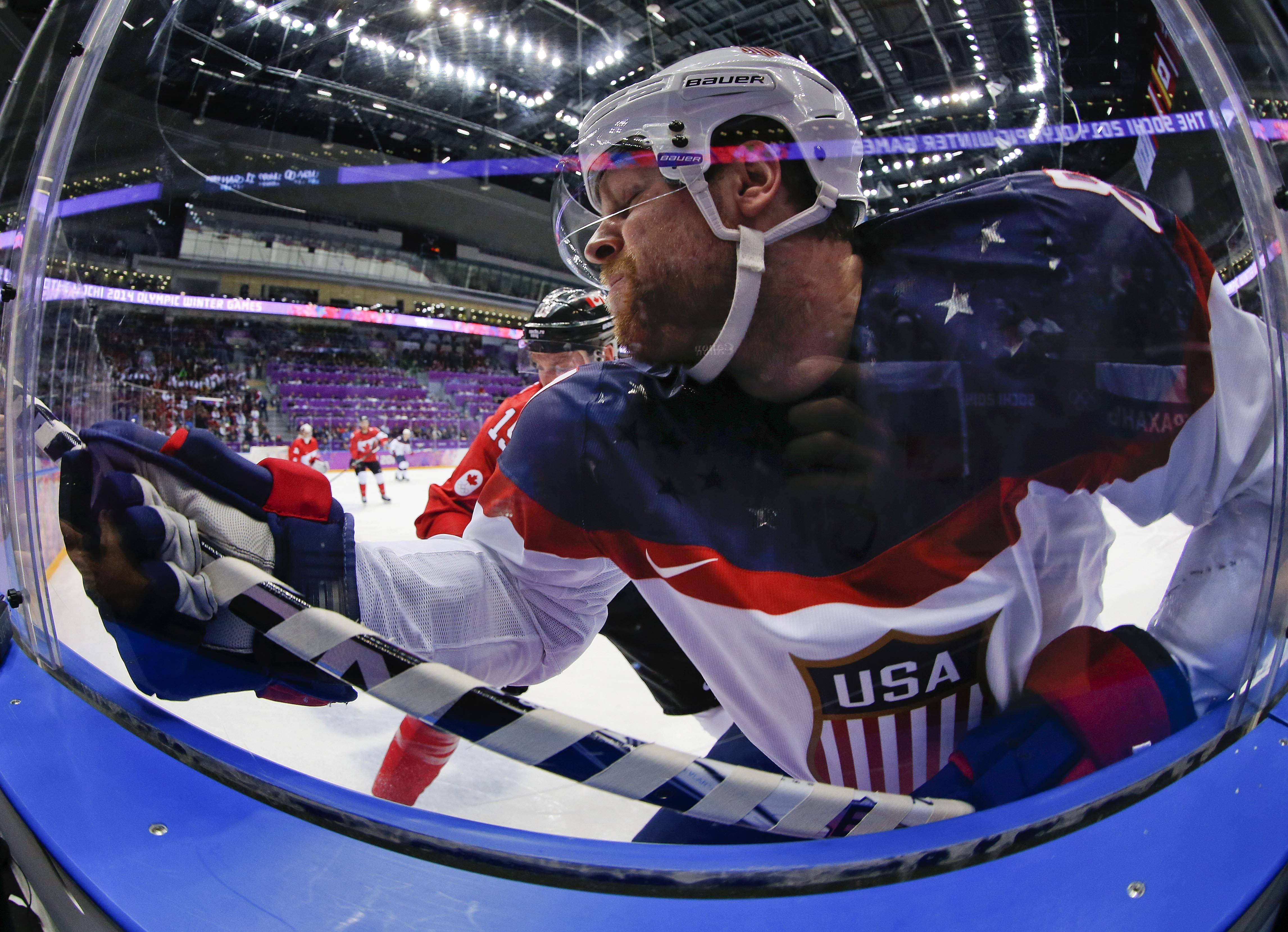 USA forward Phil Kessel crashes the boards against Canada during the second period.