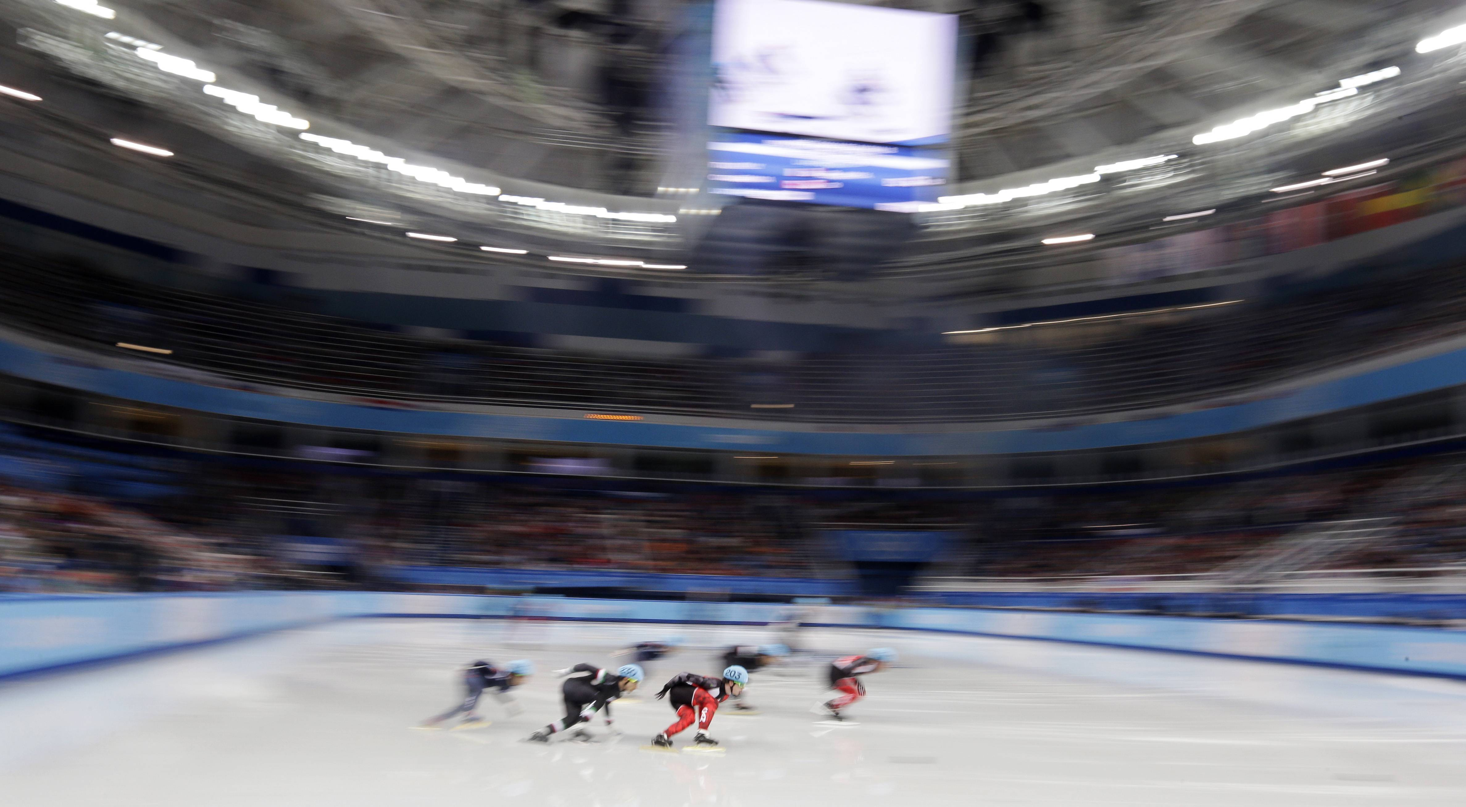 Charle Cournoyer of Canada, centre in red, competes in the men's 5000m short track speedskating relay B final.