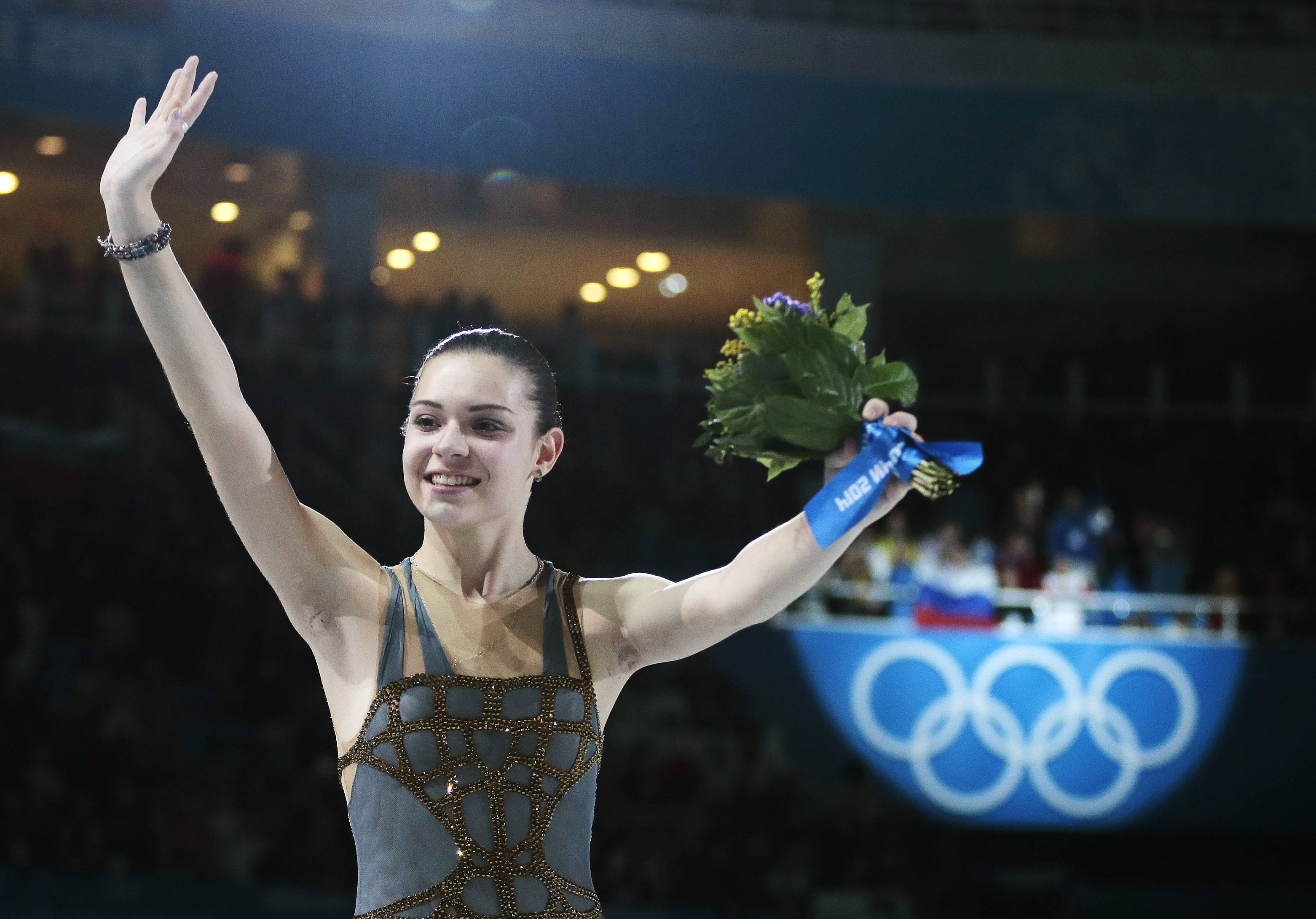 Adelina Sotnikova of Russia celebrates after placing first during the flower ceremony for the women's free skate figure skating final at the Iceberg Skating Palace during the 2014 Winter Olympics, Thursday, Feb. 20, 2014, in Sochi, Russia. Sotnikova placed first, followed by Kim and Kostner.