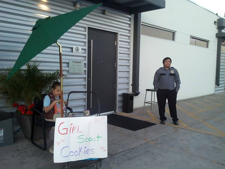 Lexi Menees, 8, sells Girl Scout Cookies while sitting Friday outside Trumed Dispensary, which sells medical marijuana for licensed patients, in Phoenix. Girl Scouts seem to be foregoing the usual supermarket stops for selling their beloved cookies.