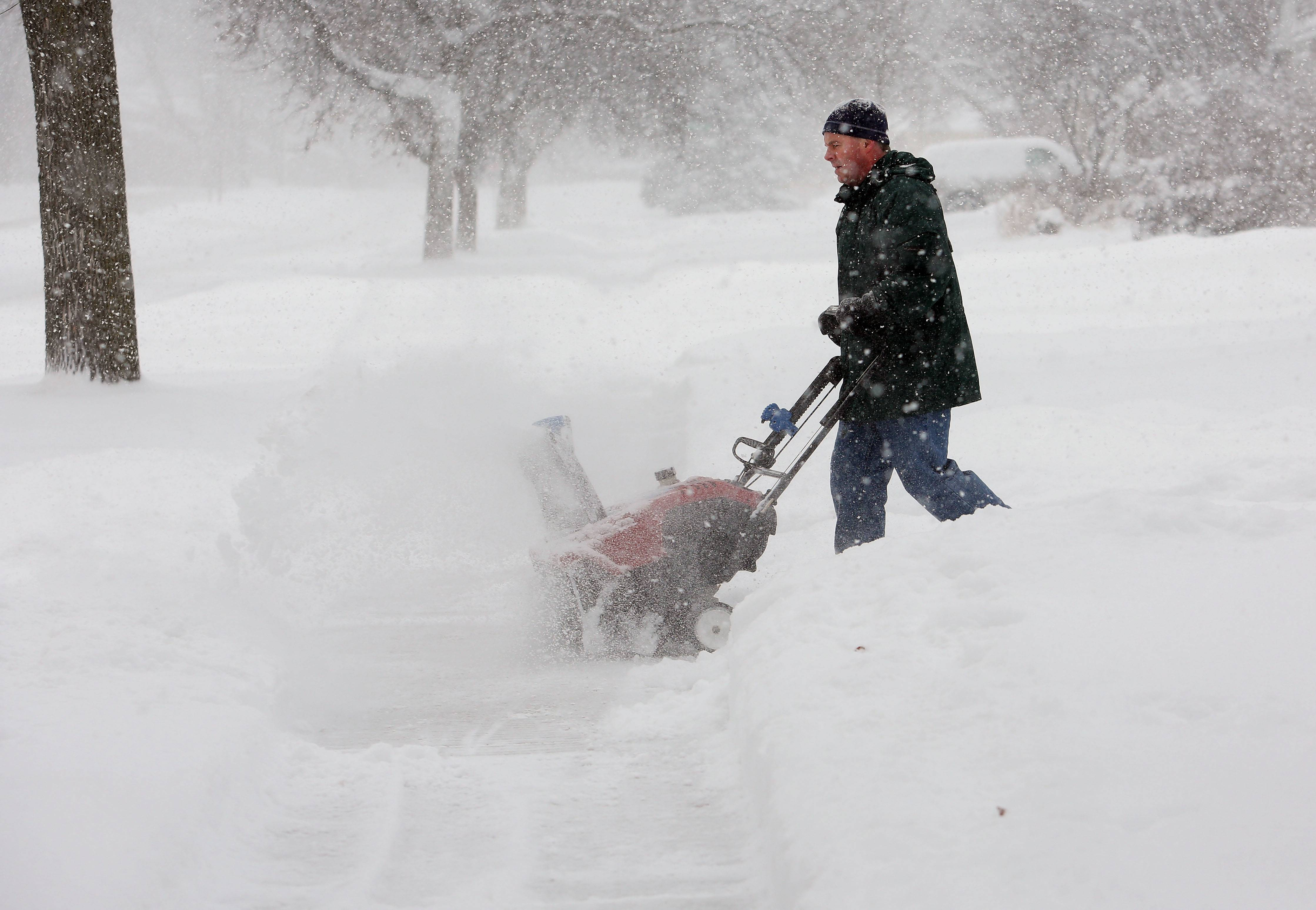 A Wheaton resident clears his driveway in early January. He and others would be out doing the same many more times before spring came.