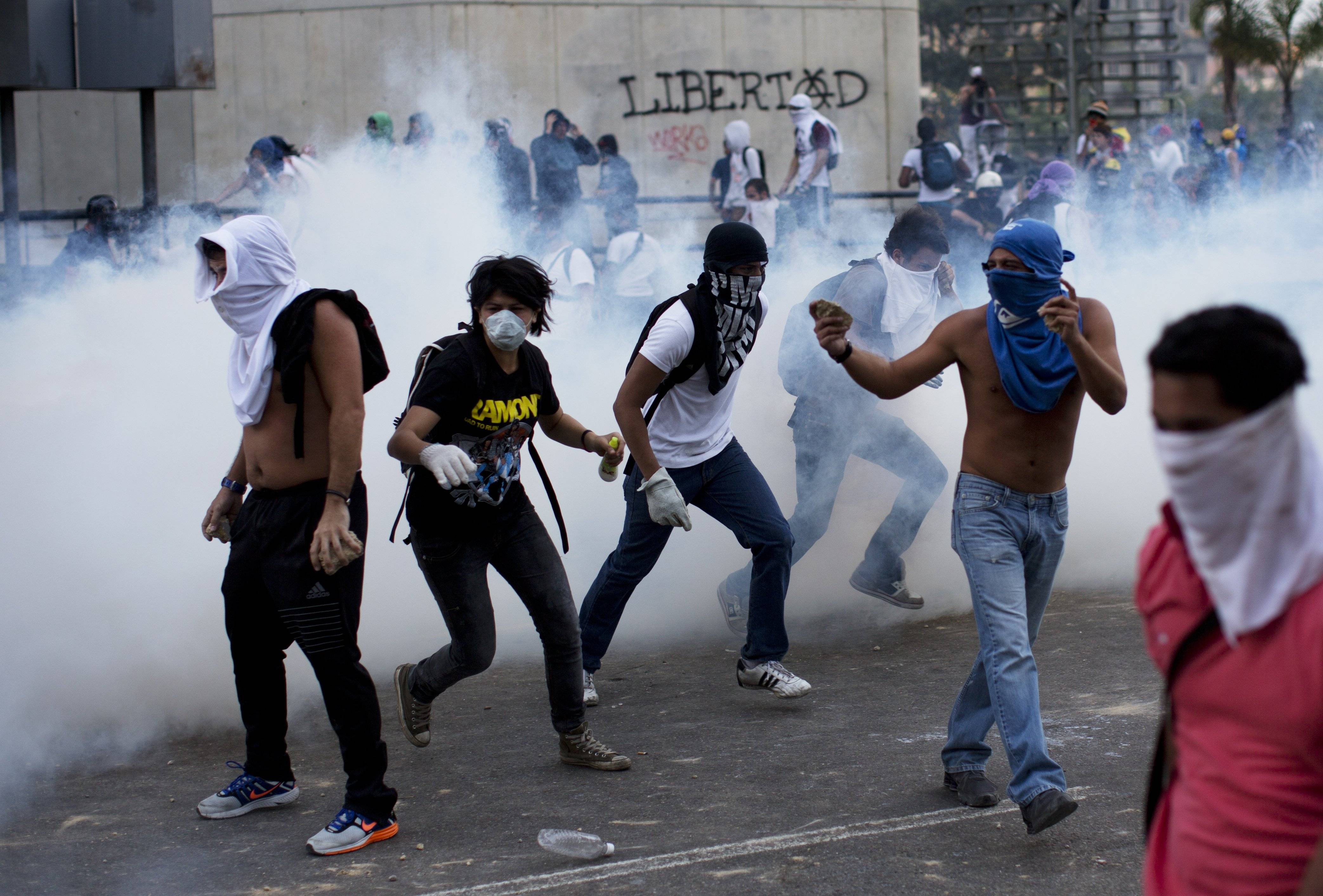 A group of masked men run for cover Saturday after riot police launched tear gas in Caracas, Venezuela. After an opposition rally broke up in the late afternoon, in a pattern that has been seen in past demonstrations, about 1,000 stragglers erected barricades of trash and other debris and threw rocks and bottles at police and National Guardsmen.