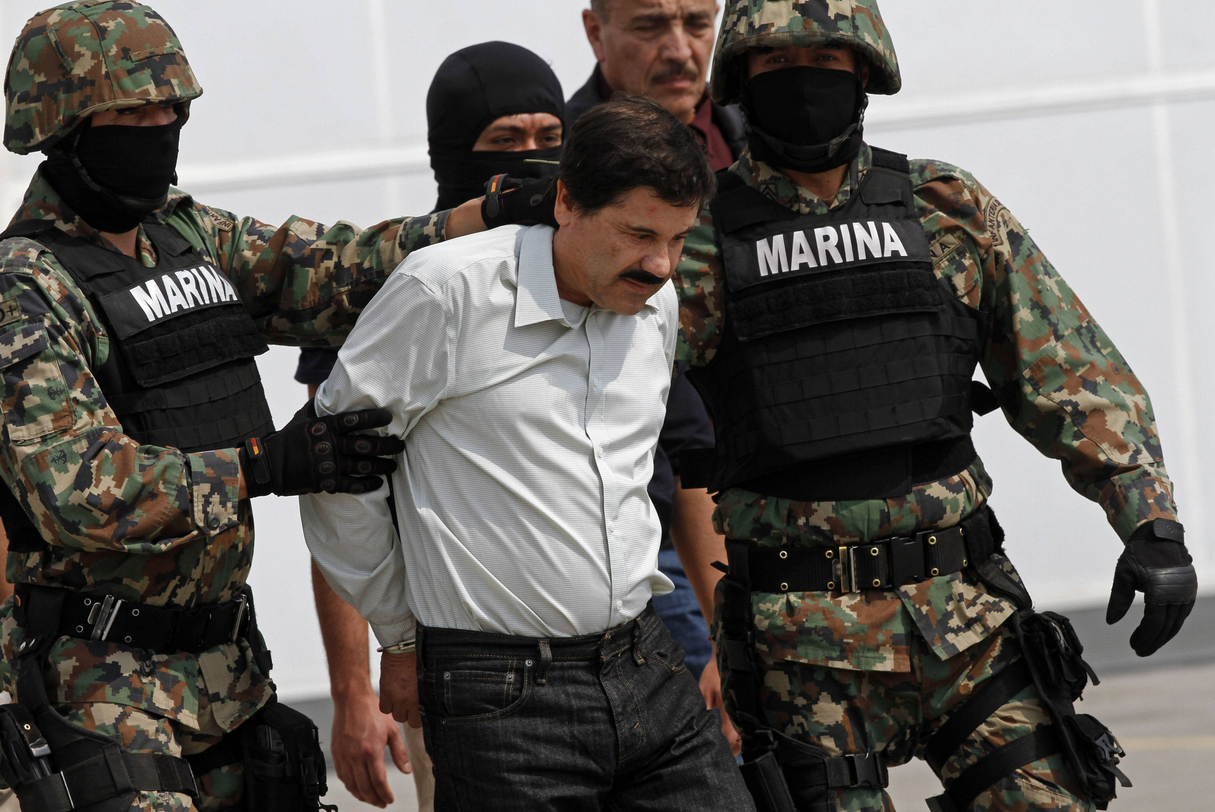 "Joaquin ""El Chapo"" Guzman is escorted Saturday to a helicopter in handcuffs by Mexican navy marines at a navy hanger in Mexico City."