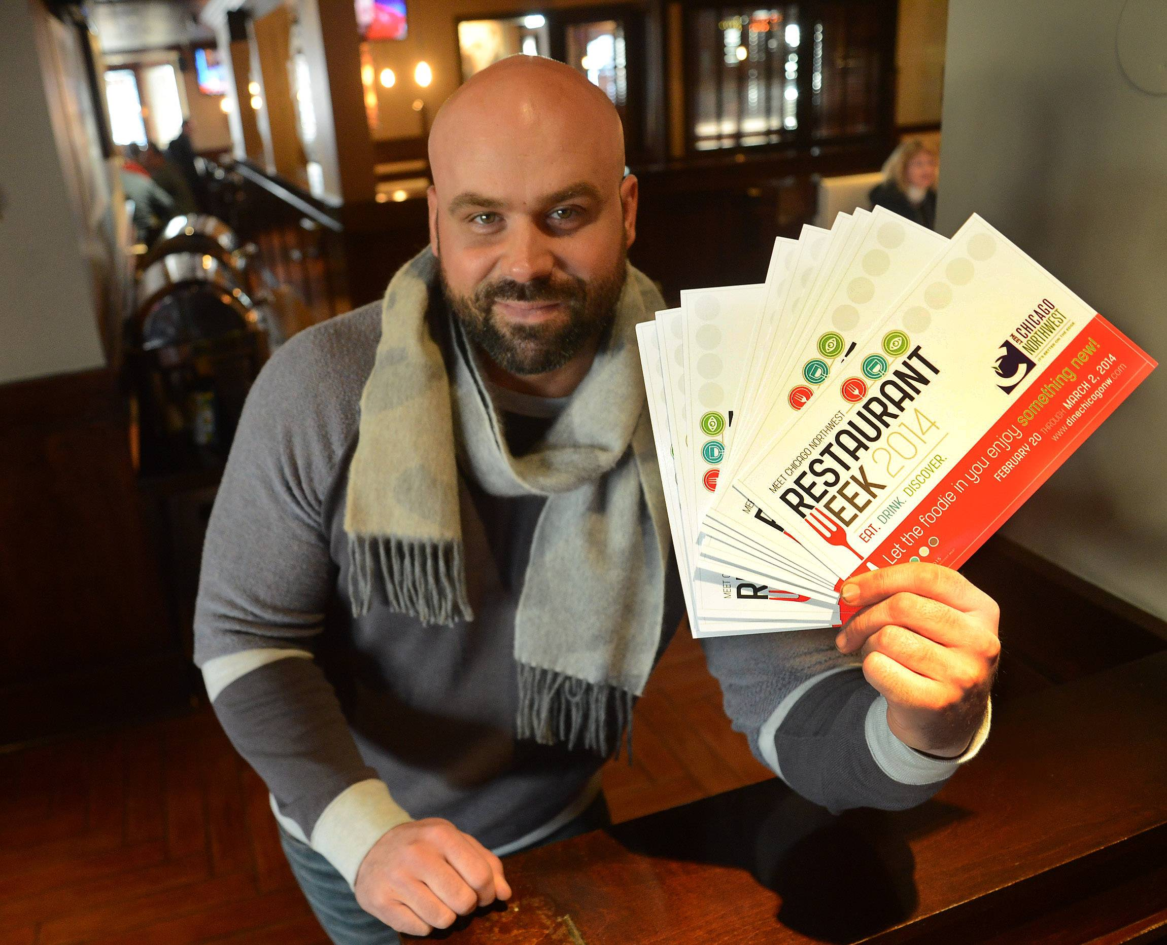 Owner Luke Johnson of the Rack House in Arlington Heights holds up Restaurant Week fliers.