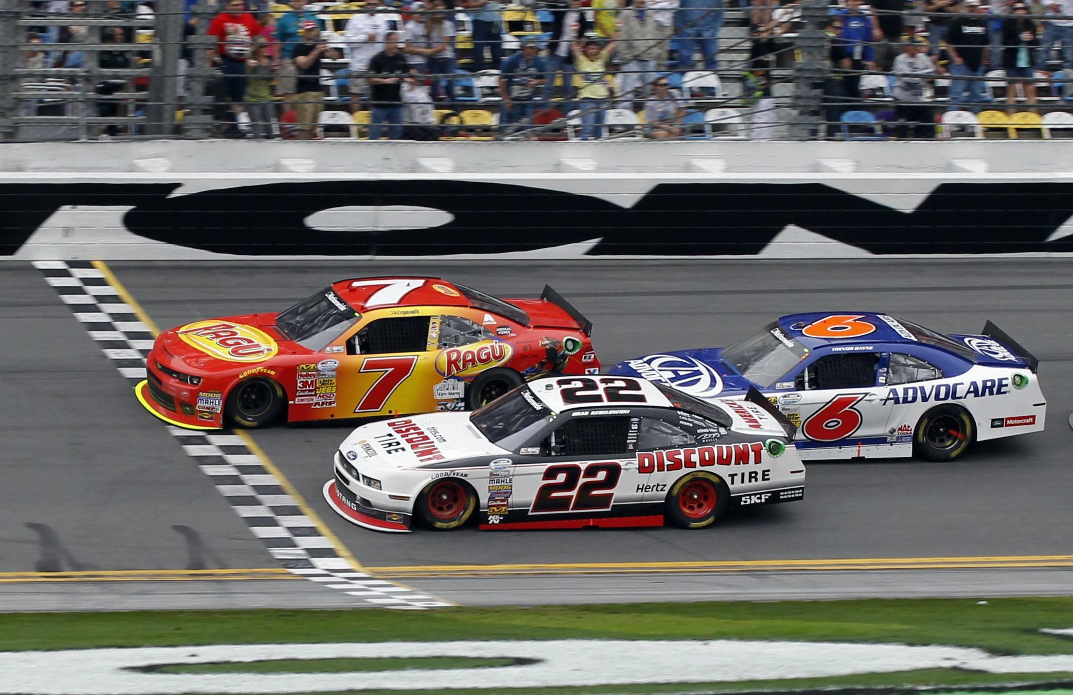 Regan Smith (7) crosses the finish line ahead of Brad Keselowski (22) and Trevor Bayne (6) to win the NASCAR Nationwide Series auto race at Daytona International Speedway in Daytona Beach, Fla., Saturday.