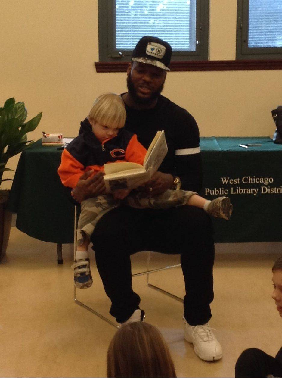 Martellus Bennett, a tight end with the Chicago Bears, reads to children at the West Chicago Public Library, with Tortsen Karlson, 4, of West Chicago, on his lap. Bennett was originally supposed to spend the afternoon playing video games with the kids but opted to spend the rest of his time reading to them.