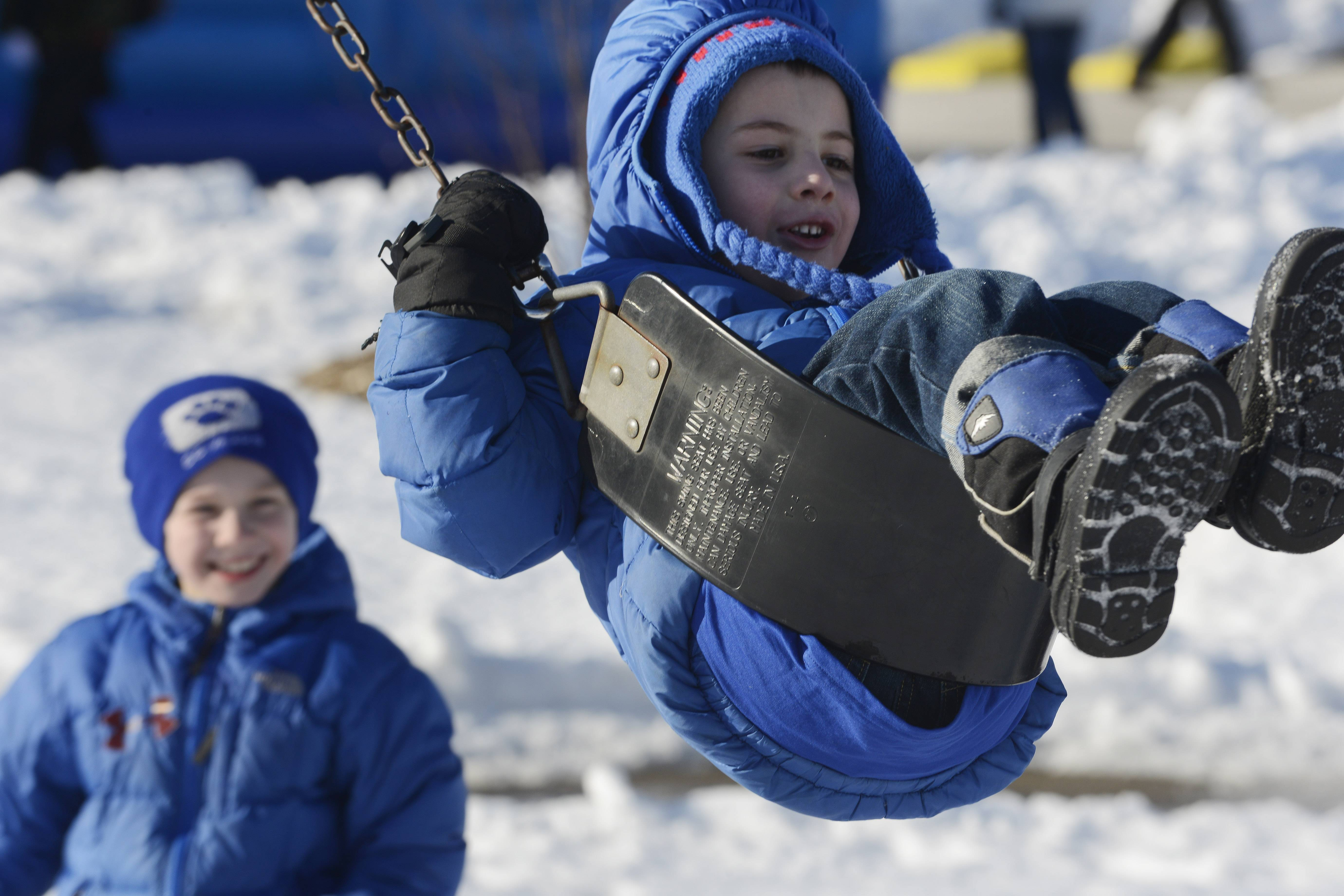 JOE LEWNARD/jlewnard@dailyherald.comLucas Harrington, 5, of Lake Zurich doesn't let the freezing temperature deter him from enjoying the swing Saturday while being pushed by his brother, Danny, 7, during the Winter Wonderland Carnival at Community Park in Hawthorn Woods.