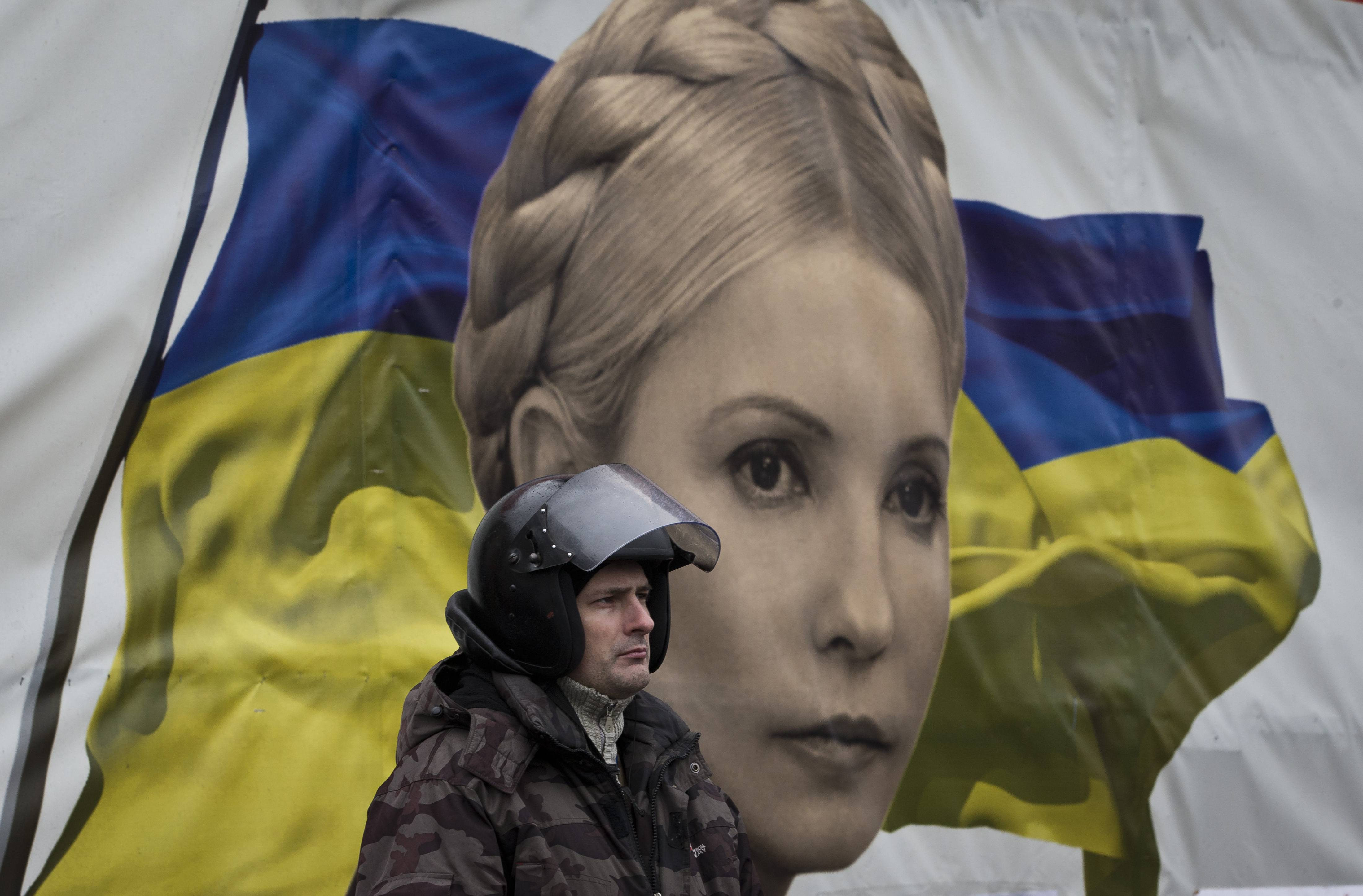 A protester stands in front of a poster Saturday of Yulia Tymoshenko, in central Kiev, Ukraine.