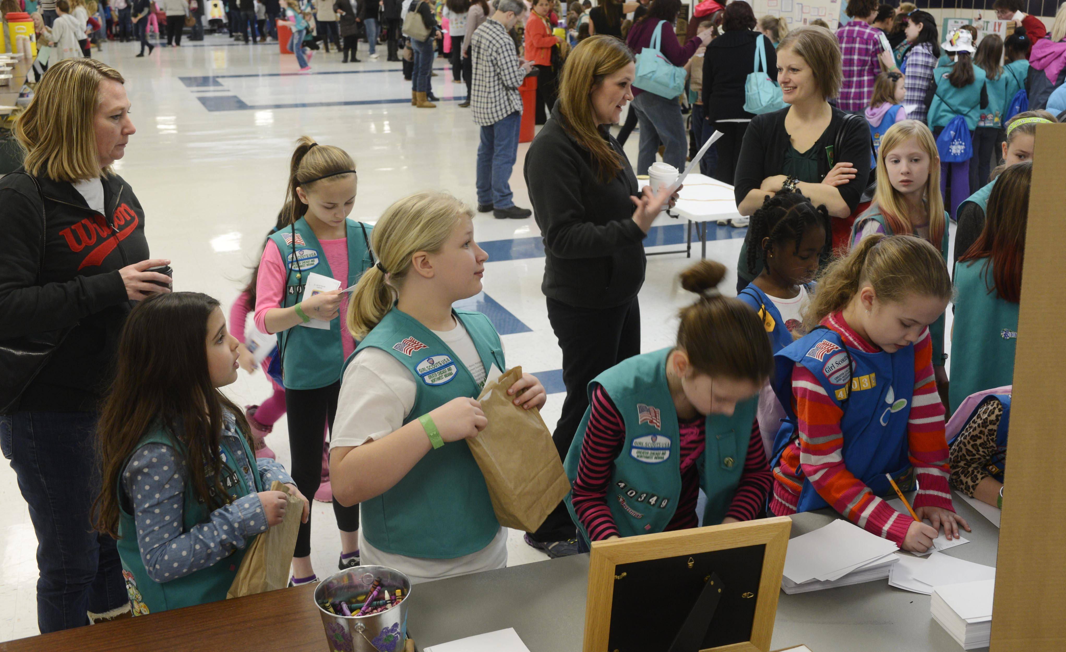 JOE LEWNARD/jlewnard@dailyherald.comGirl Scouts visit booths representing nations throughout the world Saturday morning during International Thinking Day, an international festival of sisterhood in the Conant High School cafeteria.