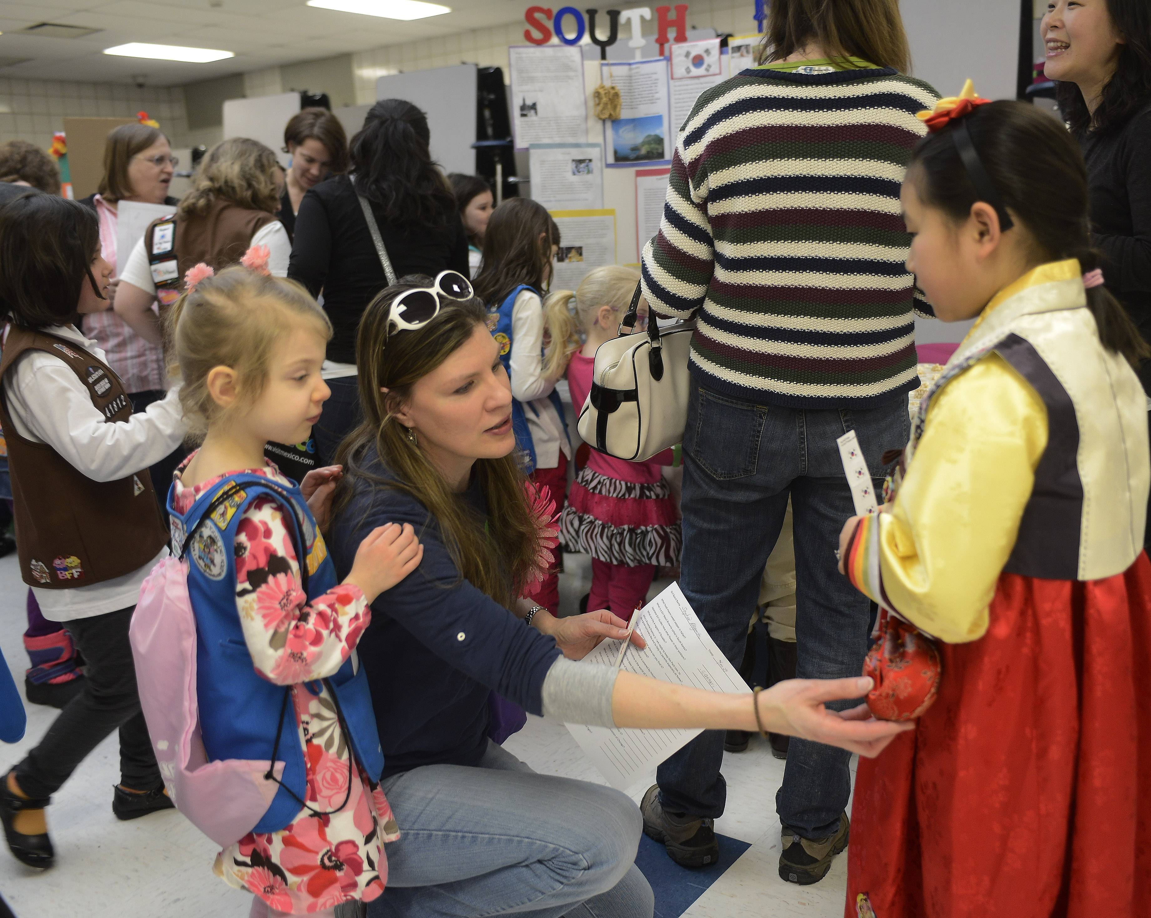 "JOE LEWNARD/jlewnard@dailyherald.comChelsie Son, 7, who lives in Schaumburg and is a member of troop 41812 in Hoffman Estates, shows the traditional clothing of South Korea to Sophia Magenta, 5, of Daisy Troop 40029, Elk Grove Village, and her mom, Laura, Saturday morning during ""Thinking Day,"" an international festival of sisterhood in the Conant High School cafeteria."