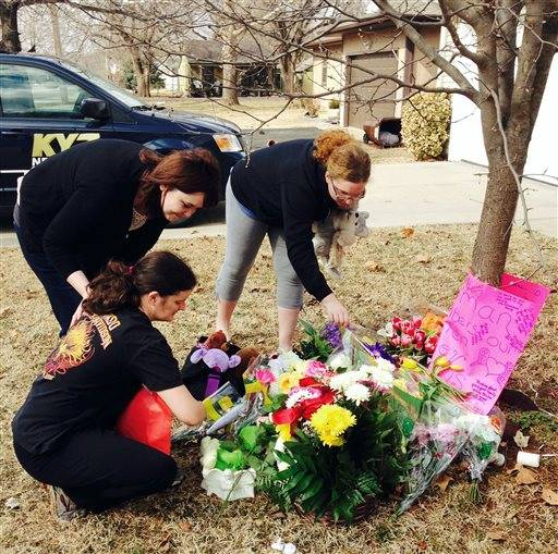 Stacey Barfield, mother of Hailey Owens, kneeling, and family members Sara Wells, left, and Teri Nord arrange flowers left by well wishers Thursday, Feb. 20, 2014 near the site where the 10-year-old girl was abducted just blocks from the Springfield, Mo., home. Prosecutors have charged Craig Michael Wood with first-degree murder, kidnapping and armed criminal action in their girls death. Prosecutors says the fourth-grader's body was found stuffed in two trash bags inside plastic storage containers in the basement of Wood's Springfield home. She had been shot in the head.
