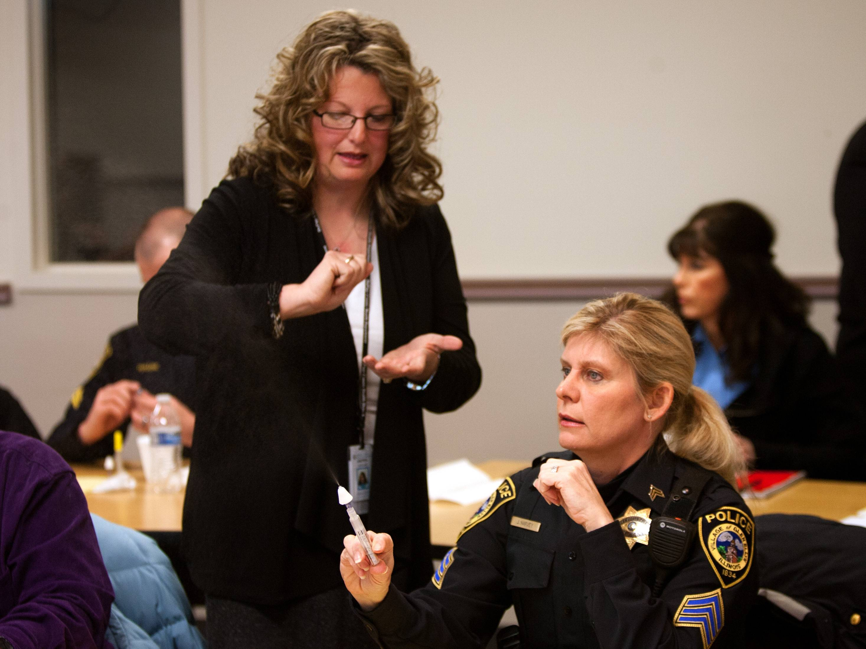 DuPage County health officials are training police officers how to administer Narcan, an opiate overdose reversal drug. Andrea Gargani, left, director of community health services, teaches the Narcan application process to Glen Ellyn police Sgt. Jean Harvey.