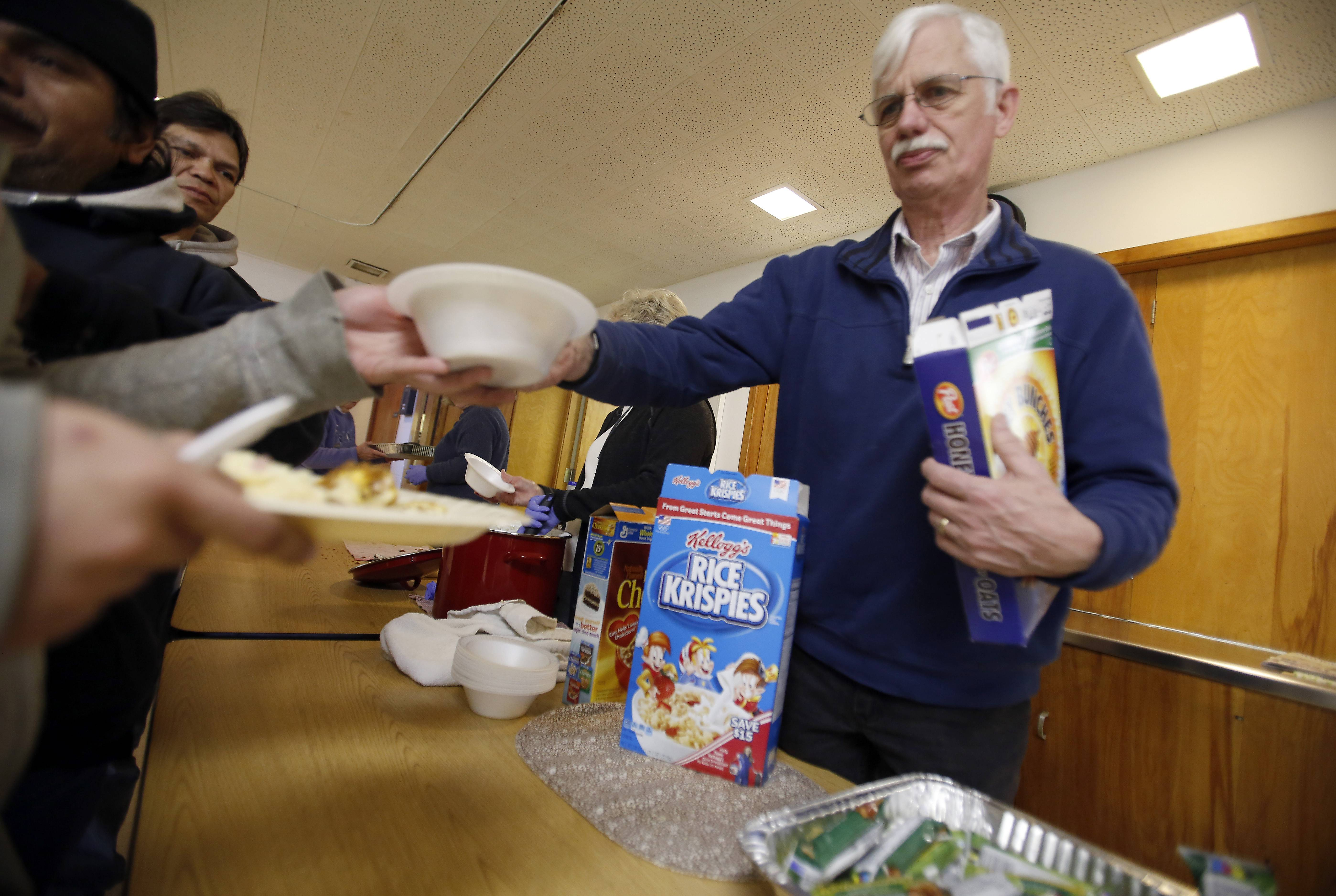 Gene Heckenberg of Algonquin hands out some cereal at a recent Vineyard Church community breakfast. In addition to helping with the meal, Heckenberg leads Bible studies, teaches computer classes, serves as a court advocate, and drives people to doctor appointments.