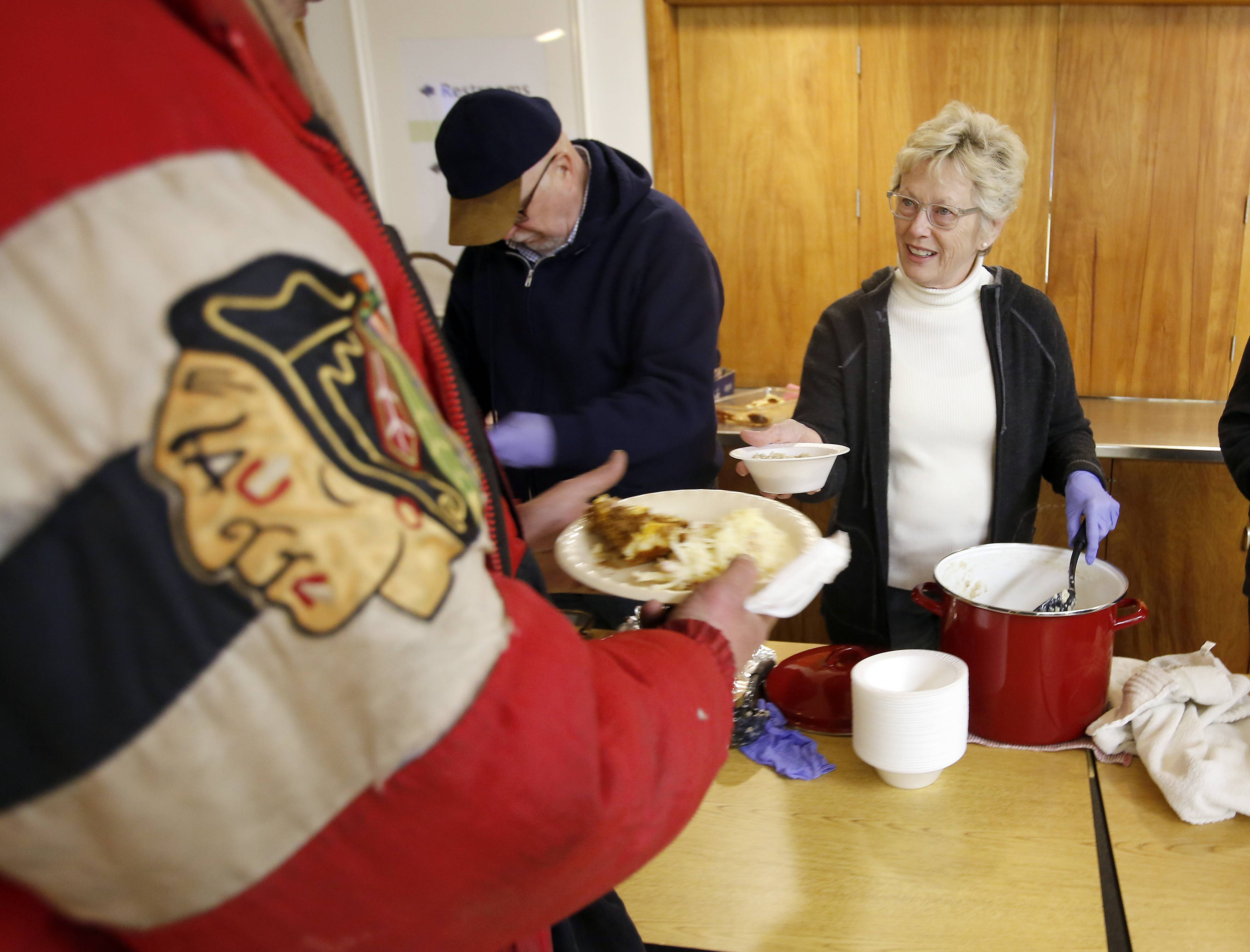 Kathy Long of West Dundee hands out some hot oatmeal as volunteers from all over serve a hot breakfast to the homeless at Vineyard Church, in Elgin.