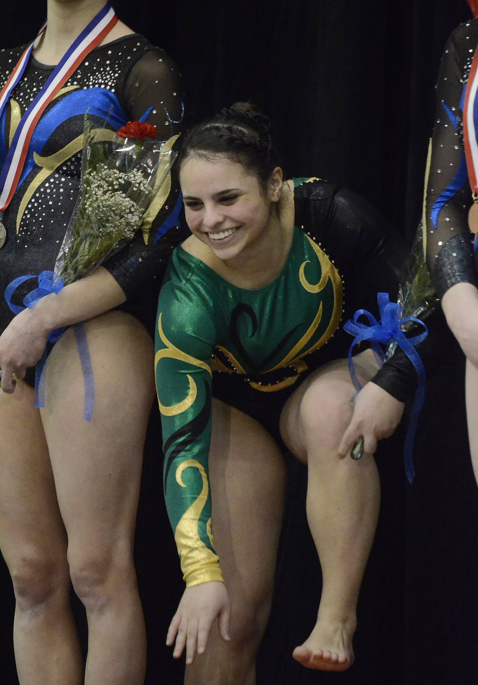 Alyssa Weisberg of Stevenson High School crawls up the podium after capturing first in the Balance Beam during State Girls Gymnastics Saturday at Palatine High School.