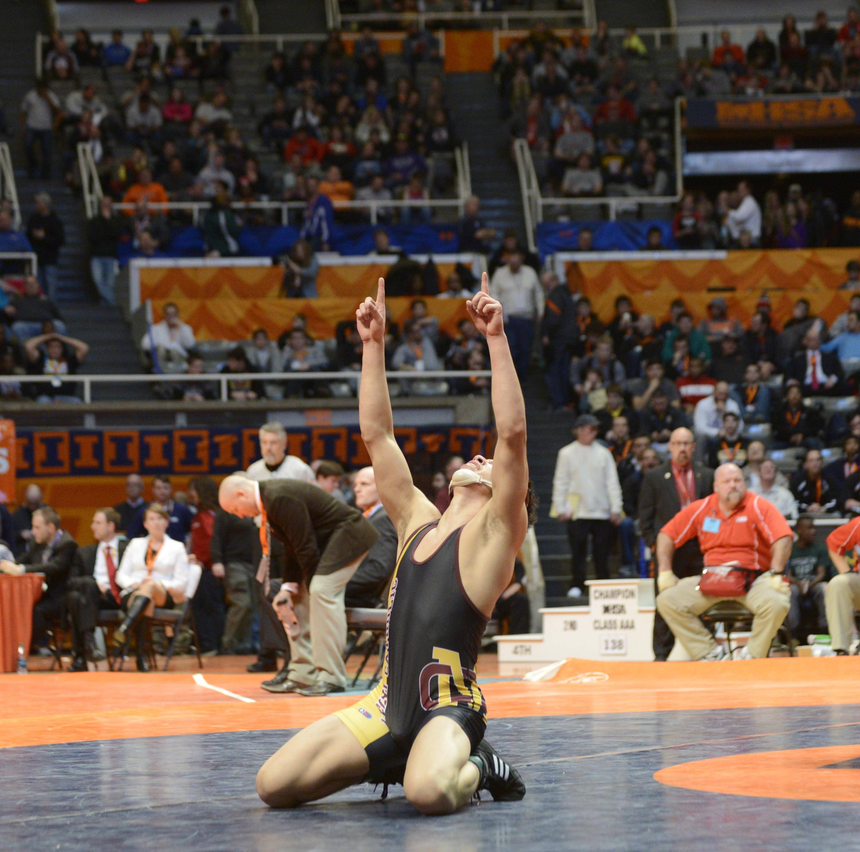 Chris Garcia of Lombard Montini Catholic High School falls to his knees after defeating SirRomeo Howard of East St. Louis High School Saturday in the 145-pound weight class championship match of the wrestling IHSA Class 2A state tournament at State Farm Center in Champaign.